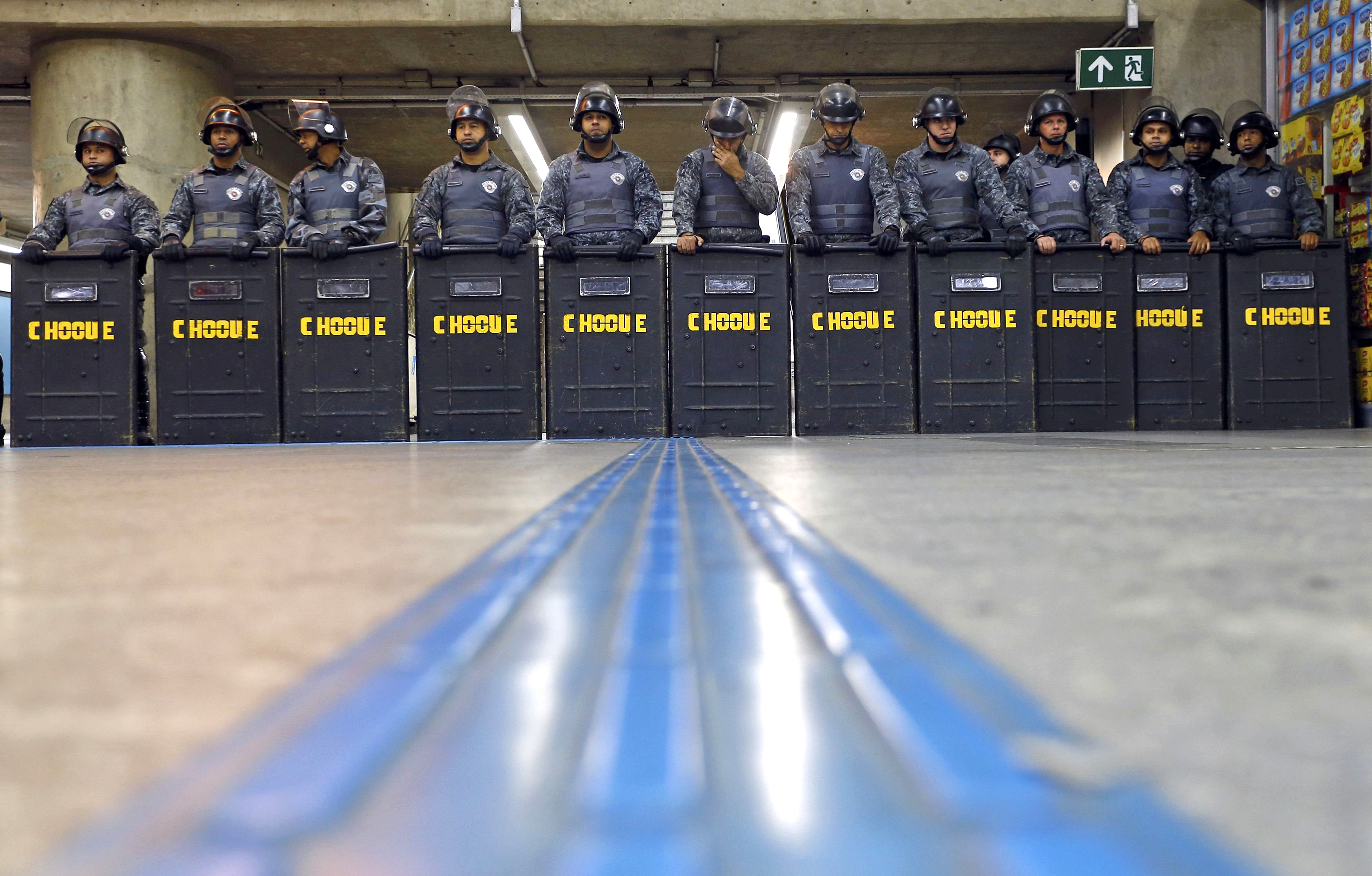 Policemen in riot gear stand inside Ana Rosa subway station during the fifth day of metro worker's protest in Sao Paulo on June 9, 2014.