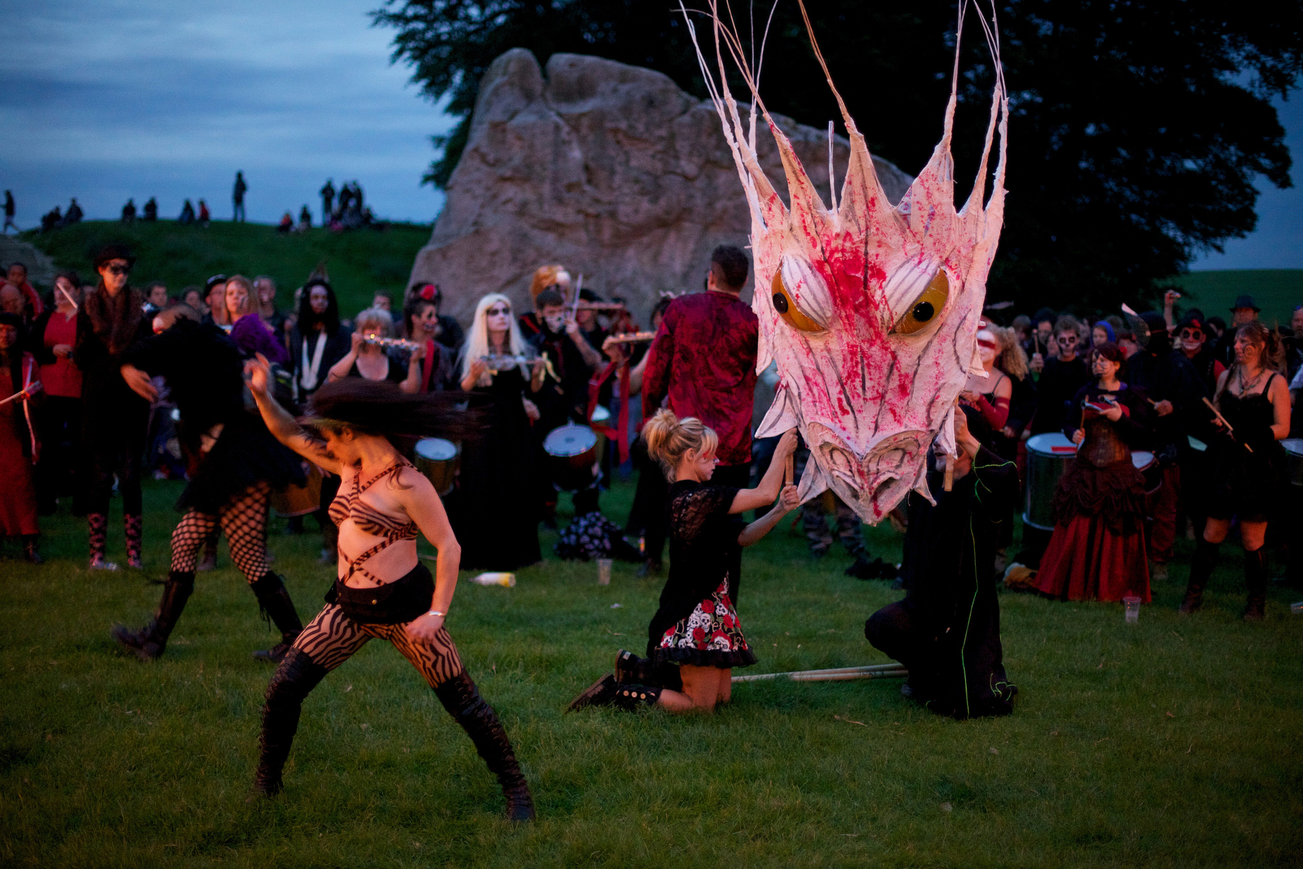 Music is played and torches are held aloft as revelers celebrate into the early hours on the summer solstice at the Avebury stone circle on June 21 2012.