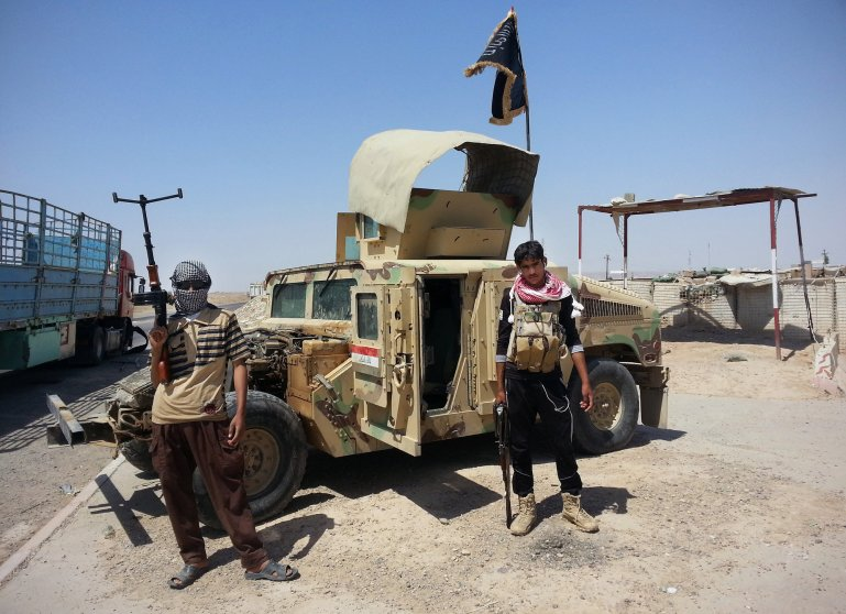 Al-Qaeda inspired militants stand with captured Iraqi Army Humvee at a checkpoint belonging to Iraqi Army outside Baiji refinery some 155 miles north of Baghdad, June 19.