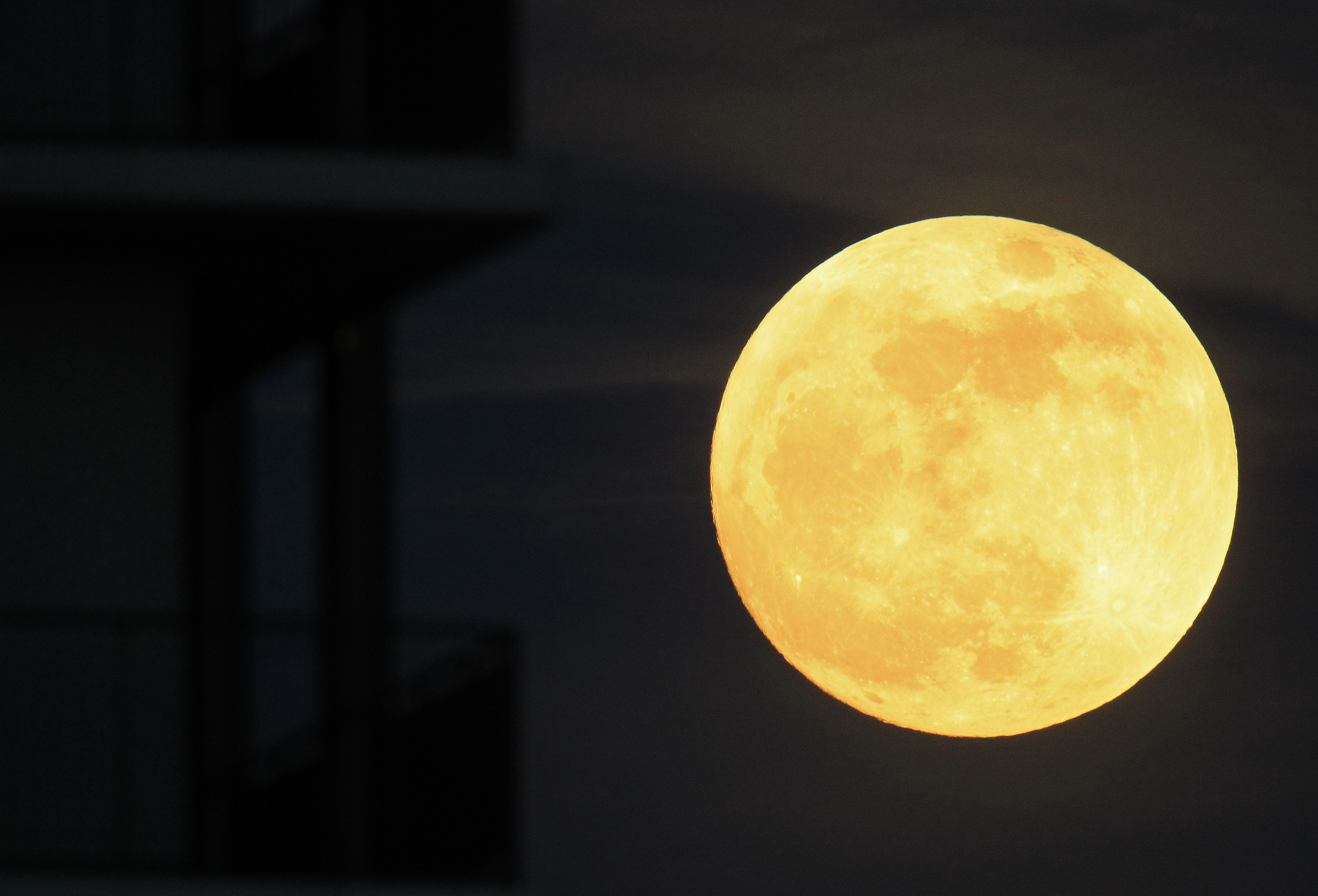 The moon rises near an apartment block in Bucharest on May 5, 2012.