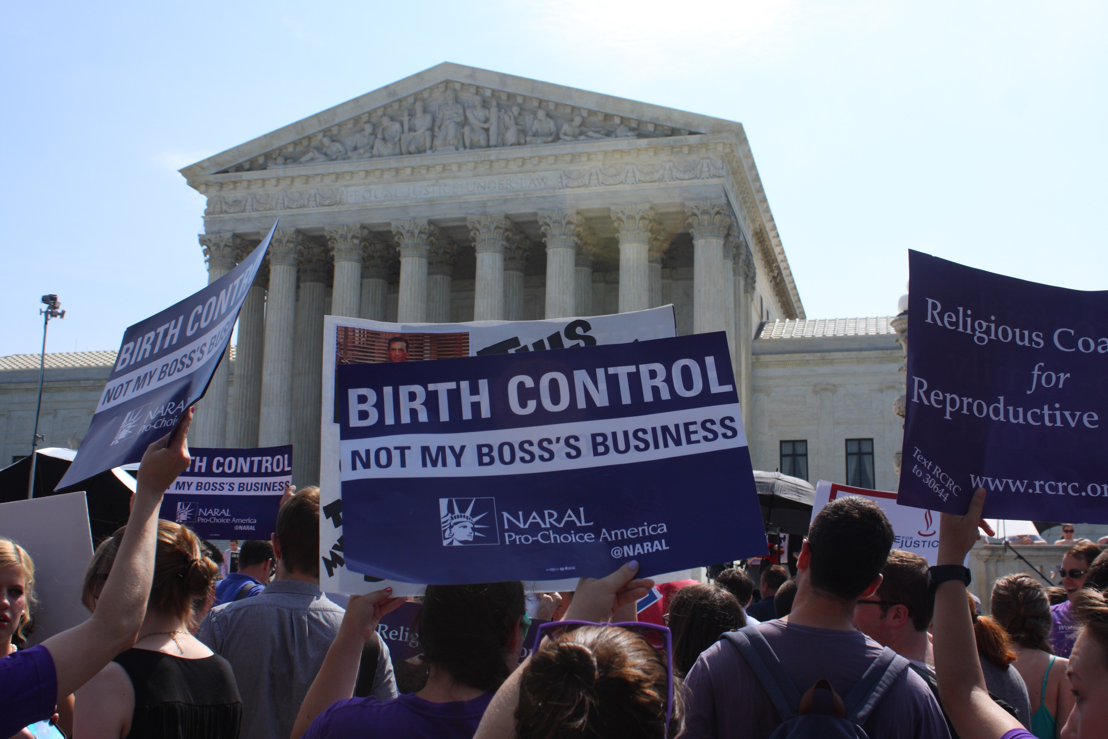 People with signs outside the Supreme Court building await a ruling in Burwell v. Hobby Lobby on June 30, 2014 in Washington.