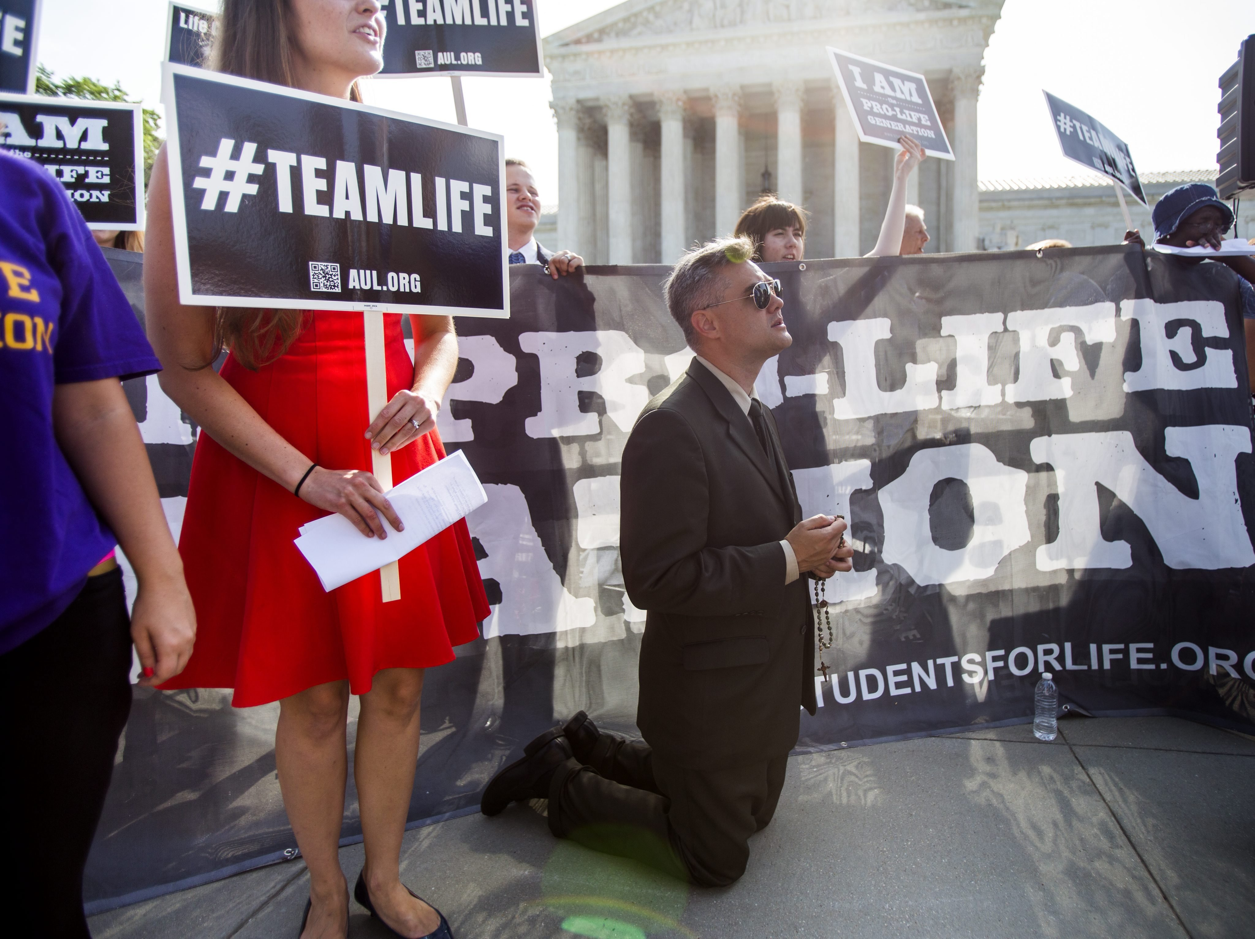 Pro-life supporter Michael Hichborn with American Life League prays outside the US Supreme Court where the nine justices are expected to issue their ruling on the Hobby Lobby case, which challenges the Affordable Care ActÕs mandate that employee health plans include pregnancy preventive services, in Washington on June 30, 2014.