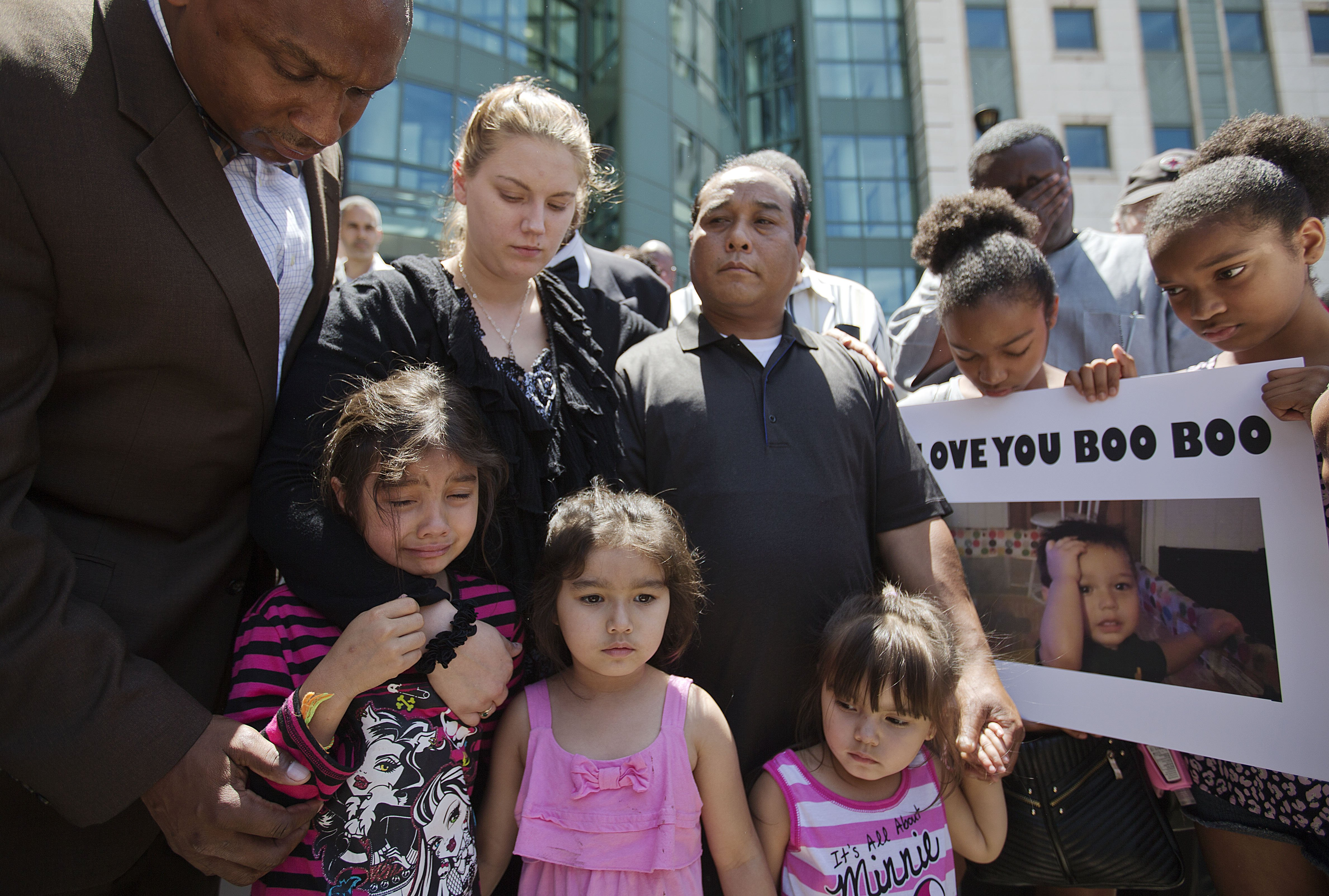 Alecia and Boun Khan Phonesavanh (center), the parents of 19-month-old Bounkham Phonesavanh who was severely burned by a flash grenade during a SWAT drug raid, attend a vigil with their daughters outside Grady Memorial Hospital where he is undergoing treatment, on June 2, 2014, in Atlanta.