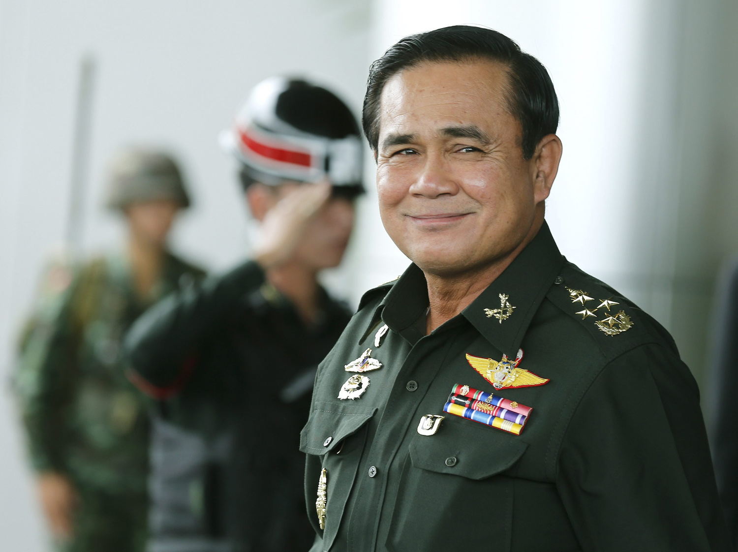 Thai army chief and junta head General Prayuth Chan-ocha smiles as he leave after the meeting of the 2015 national budget at the Army Club in Bangkok, June 13, 2014.