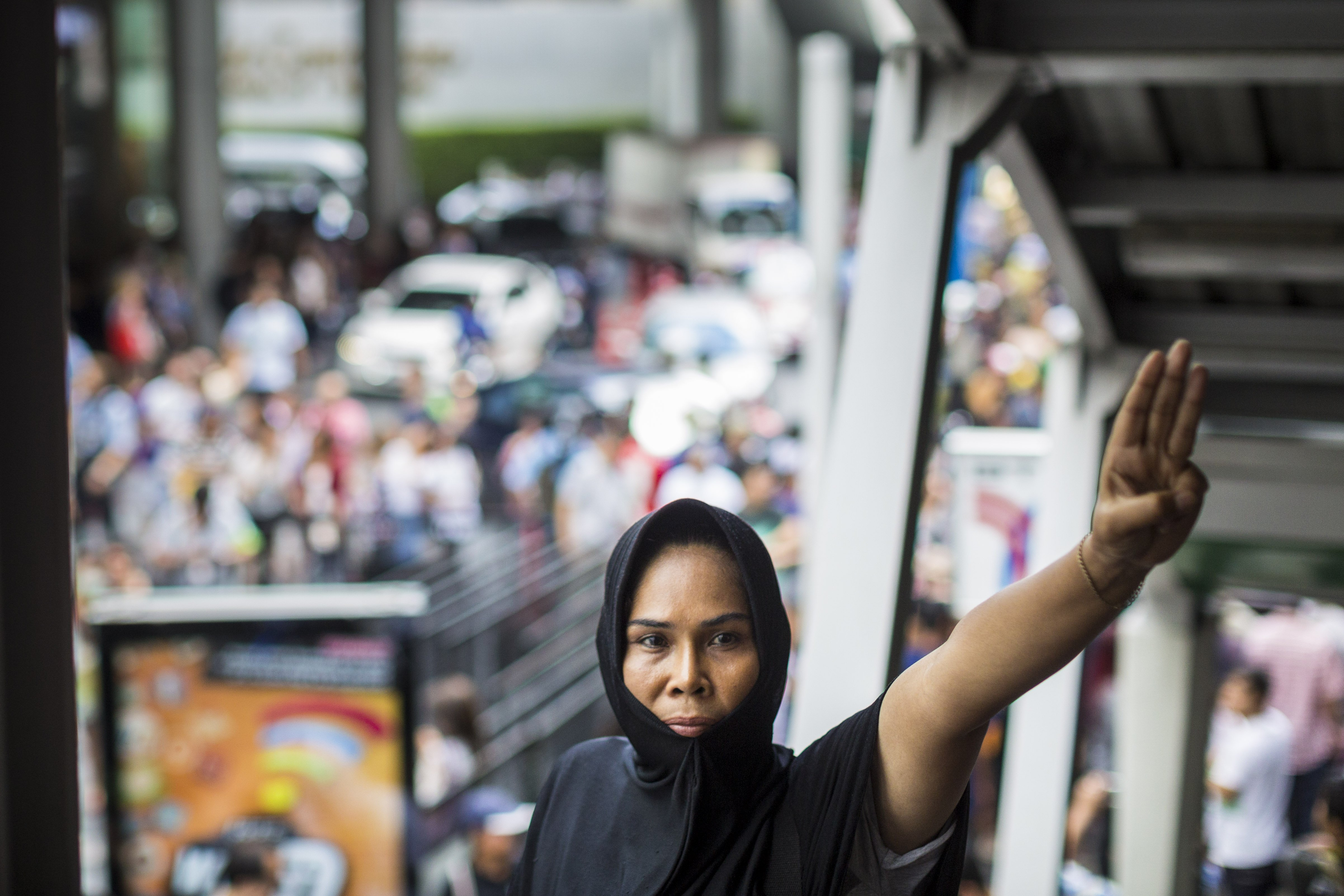 A woman holds up a three fingered salute during a protest against the Thai military coup at Terminal 21, a popular shopping mall in Bangkok, on June 1, 2014.