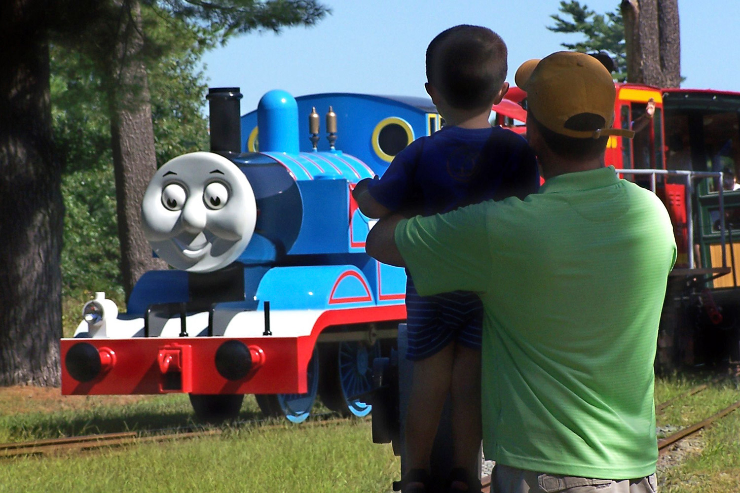 In this 2012 photo provided by Edaville USA, a father and son watch Thomas the Tank Engine roll down the track at an annual Day Out with Thomas event at the Edaville USA theme park in Carver, Mass.