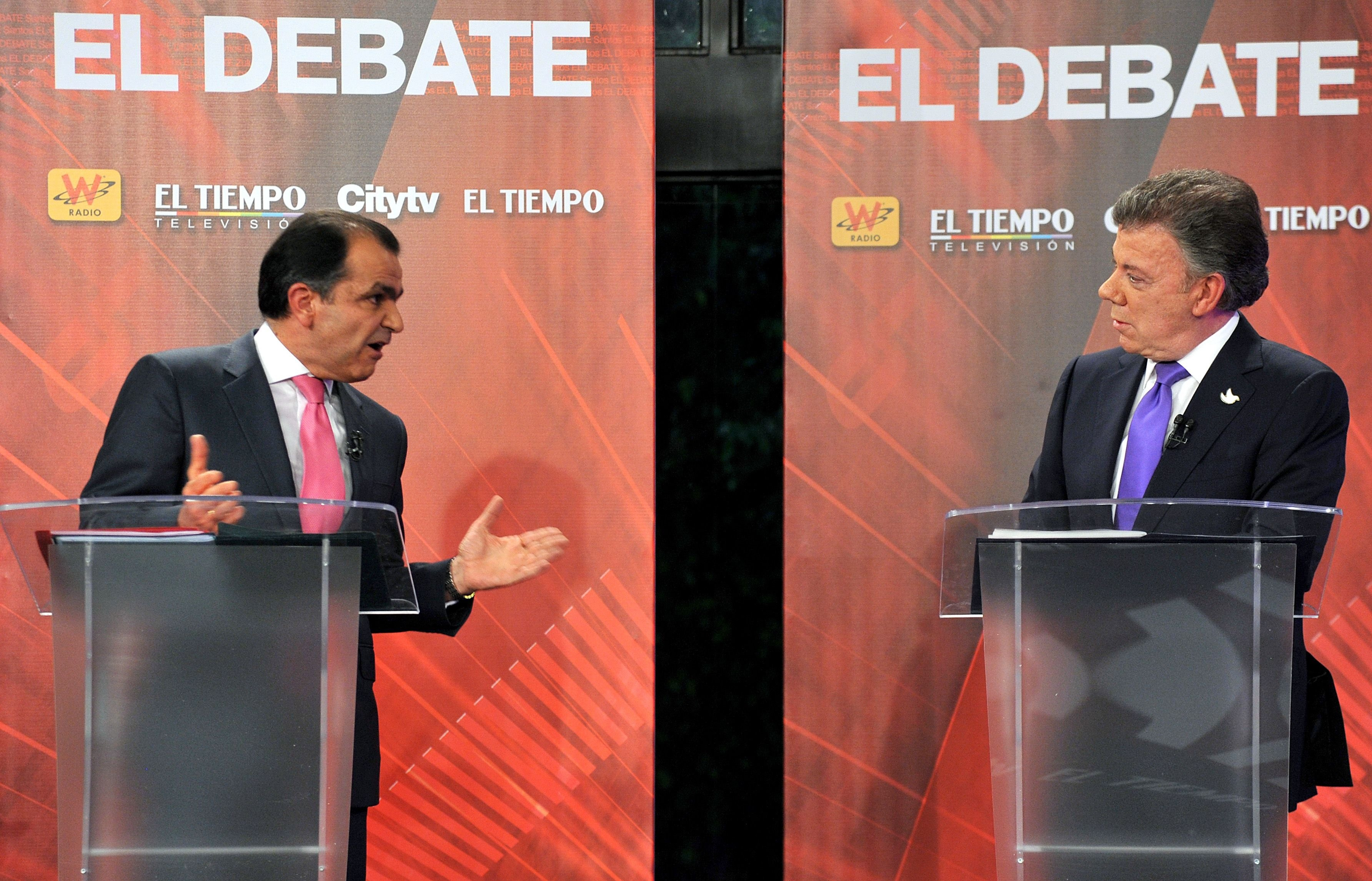 Colombia's President and presidential candidate Juan Manuel Santos (R) and Colombian presidential candidate for the Democratic Center party Oscar Ivan Zuluaga talk during a TV debate in Bogota, on June 9, 2014.