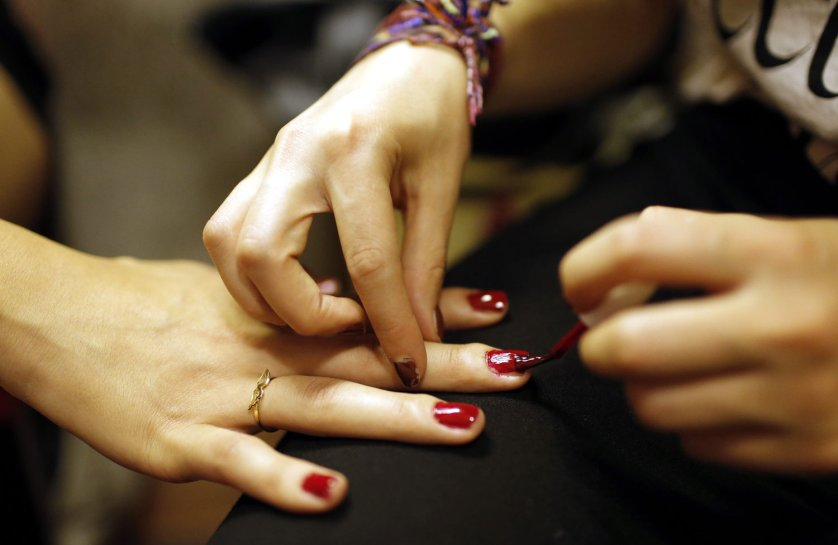A contestant gets a manicure as other contestants prepare backstage in Istanbul on June 21, 2014.