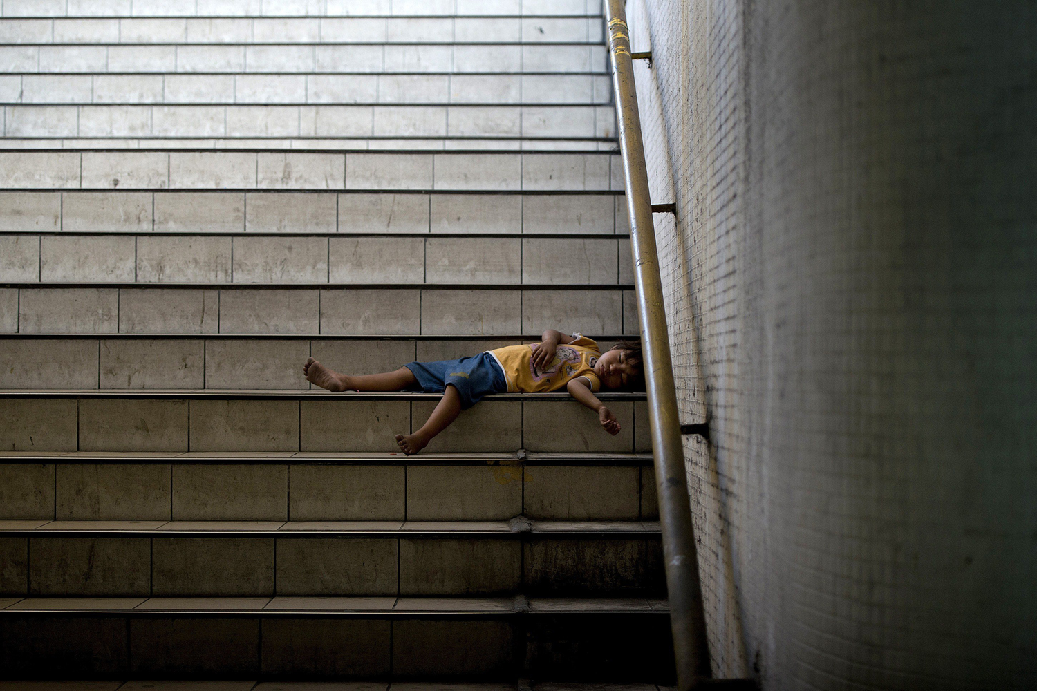 Jun. 25, 2014.                               A child sleeps on the steps of an underpass in Manila. The Philippines' roaring economy cooled in the first quarter of the year as the impacts of Super Typhoon Haiyan and other natural disasters hit harder than expected, official data showed.