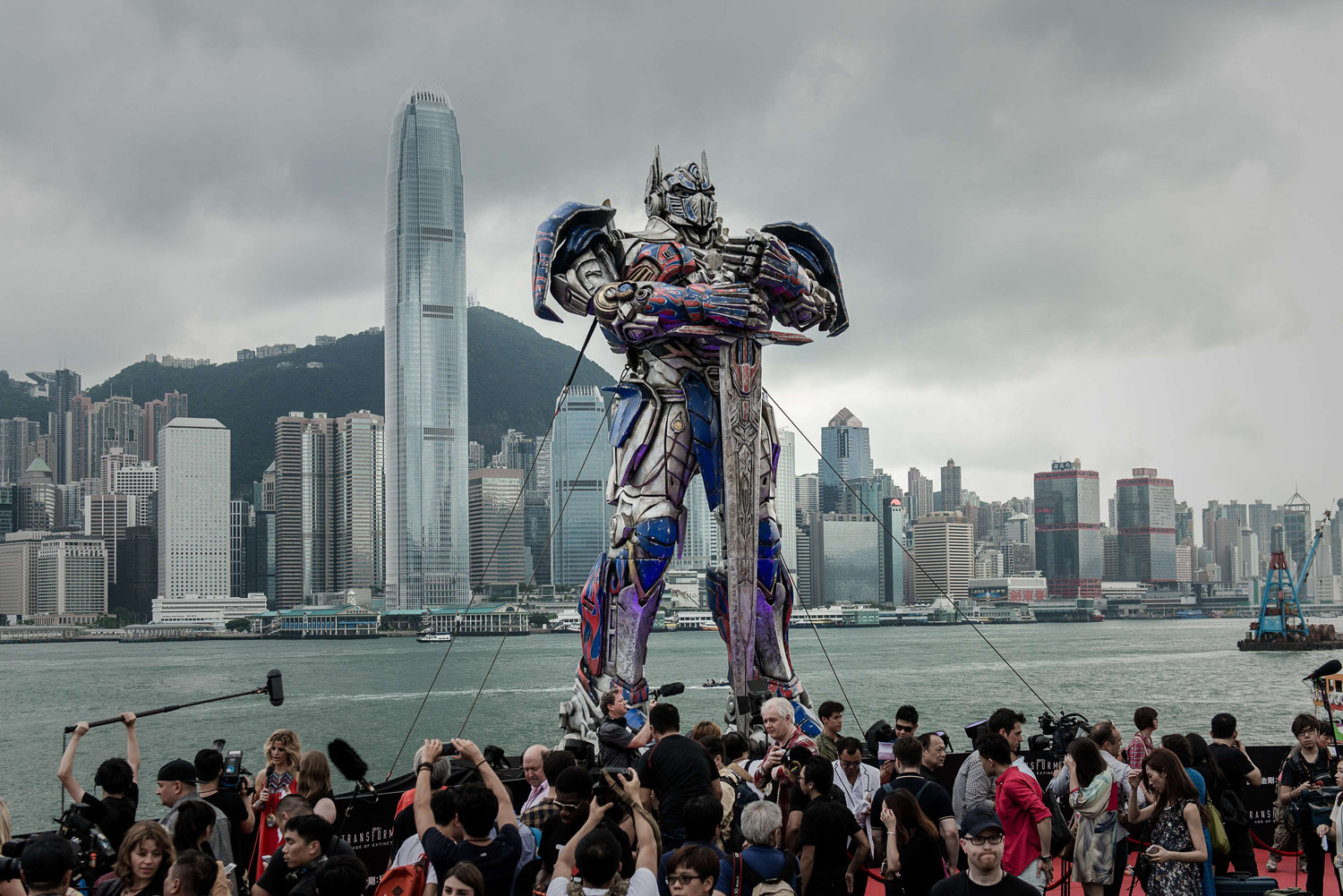 A 20 foot-tall Optimus Prime figure is surrounded by journalists before the world premiere of Hollywood movie Transformers 4 in Hong Kong on June 19, 2014.