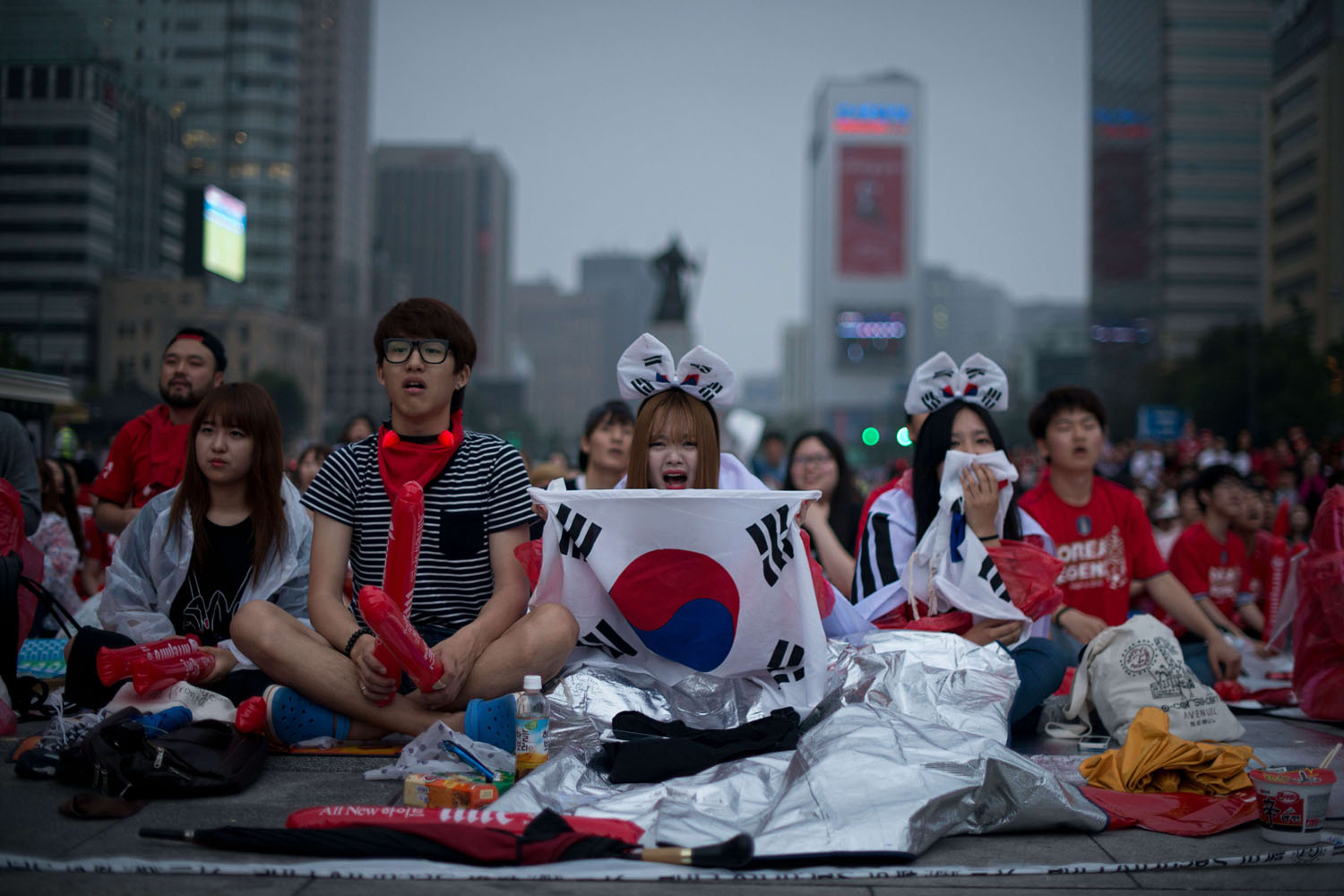 Jun. 23, 2014. South Korean football fans react as their team loses to Algeria in the 2014 World Cup in Brazil, as they watch the match on giant screens in central Seoul.