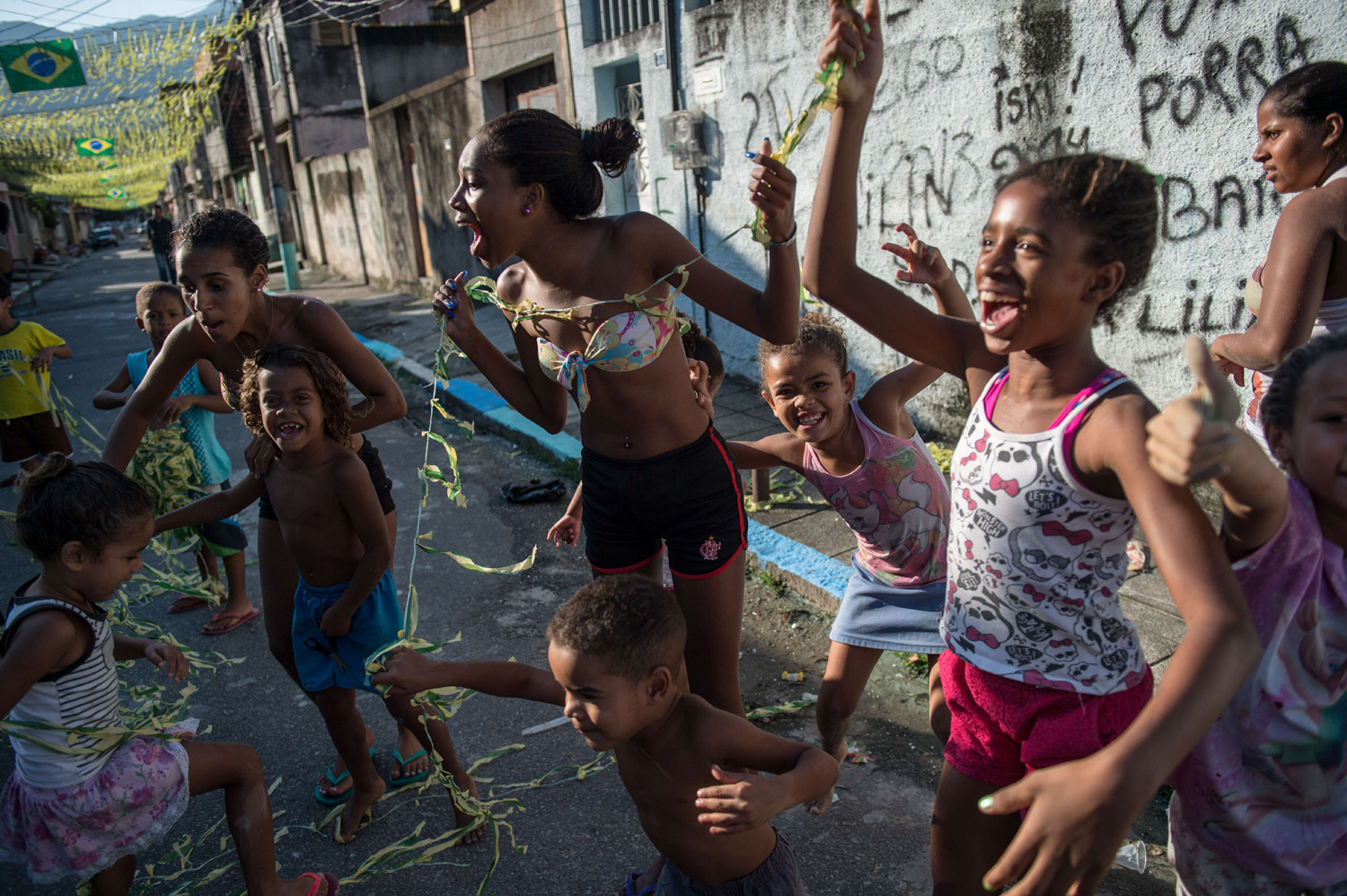 Girls help help to decorate a street for the FIFA World Cup 2014 on the eve of the opening event in Rio de Janeiro on June 11, 2014.