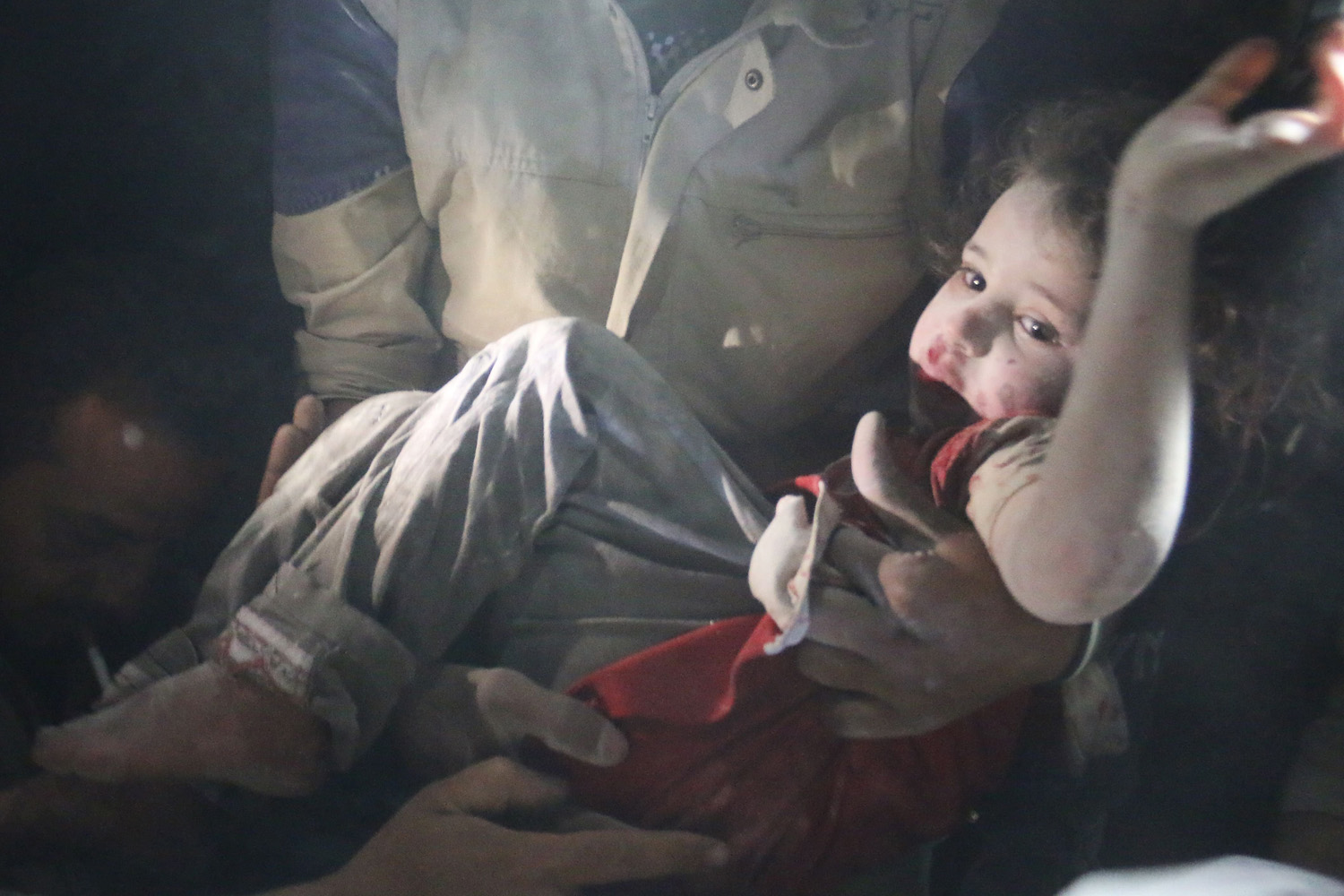 June 1, 2014. Syrian rescue workers pull out a girl from the rubble following reported barrel bomb attacks by government forces in the northern city of Aleppo.