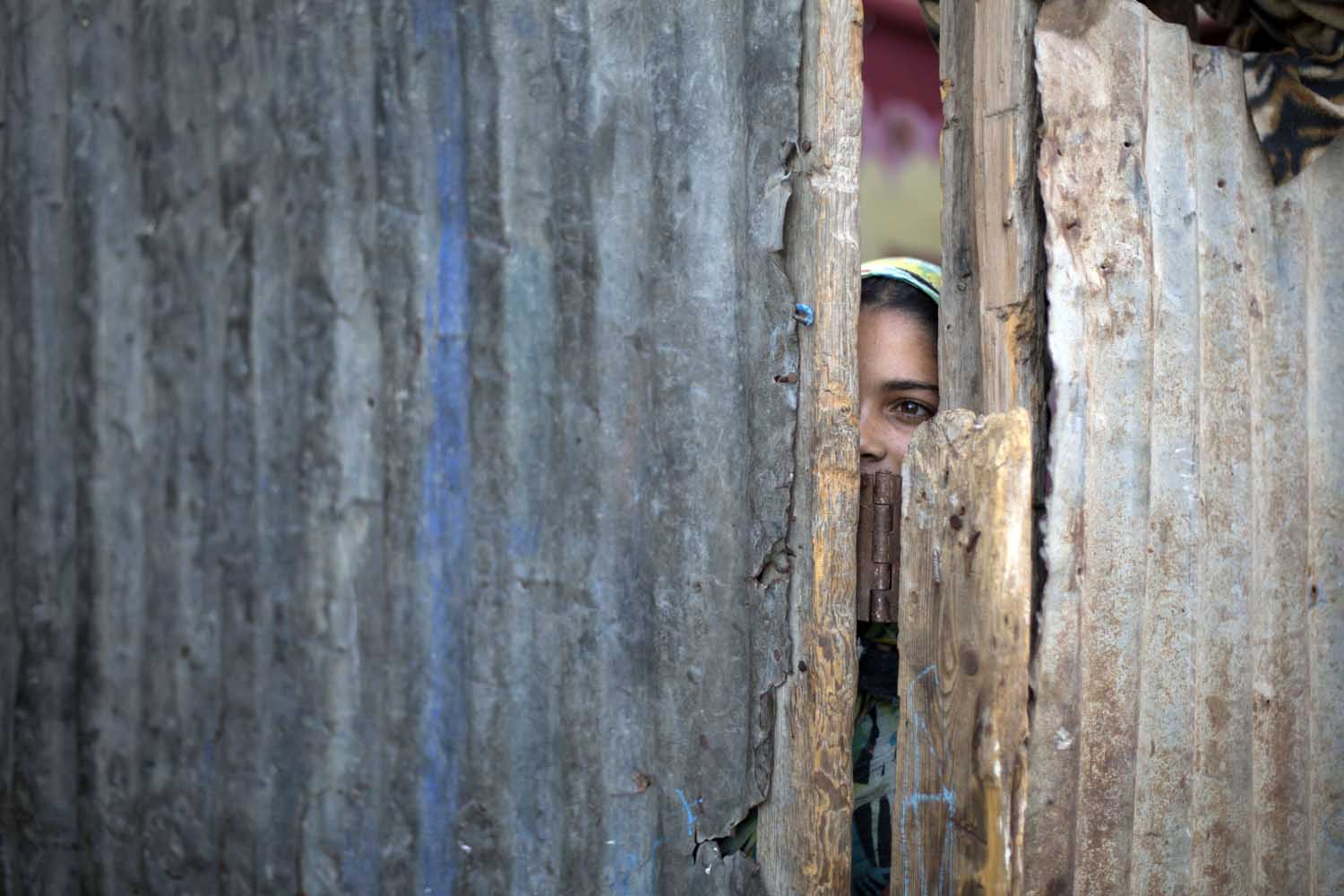 Jun. 10, 2014.                                A Palestinian girl peeps through the gate of ther home in Beit Lahia, in the northern of Gaza Strip. Some 1.6 million Palestinians live in the Gaza Strip, of whom almost 1.0 million are UN-registered refugees who were driven from or left their homes during the 1948 Arab-Israeli War.