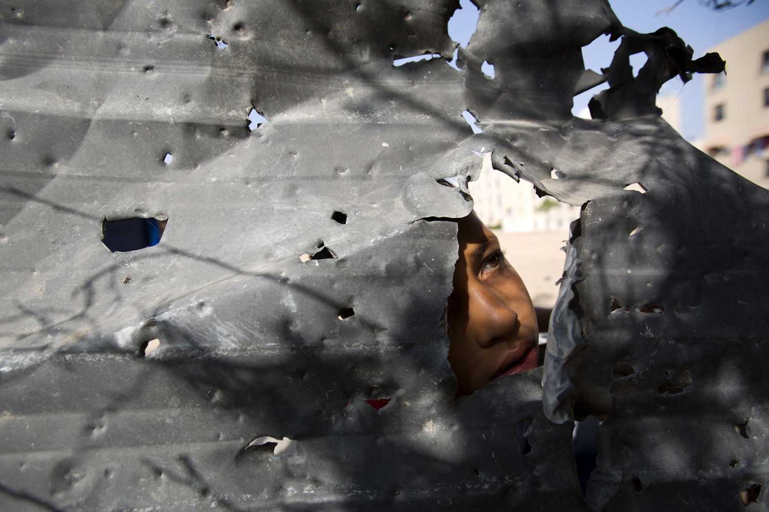 Jun. 19, 2014. A Palestinian boy peers from behind a shrapnel riddled metal piece following an Israeli air strike in the Gaza Strip's northern Beit Lahia town.