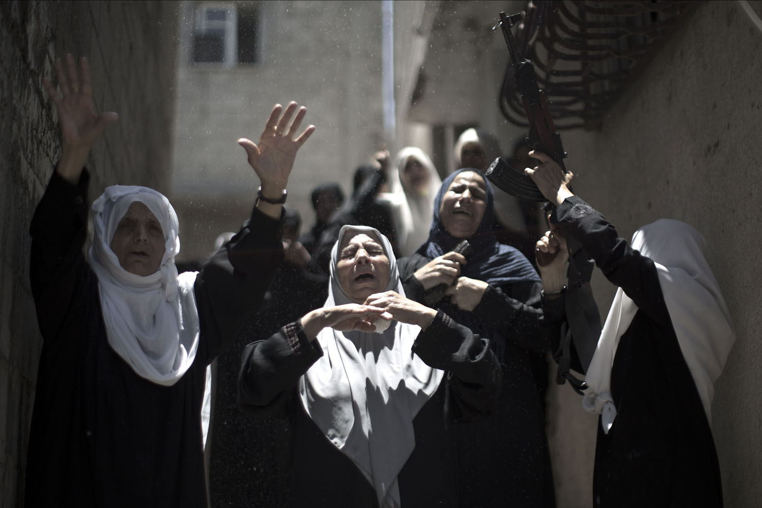 Jun. 21, 2014.                                Relatives holding a weapon mourn during the funeral of Ibrahim al-Arqan, a Palestinian member of the Ezzedine al-Qassam Brigades, the military wing of Hamas, who died two days ago after an explosion caused the collapse of a tunnel under the Israeli border, on  in Gaza City.