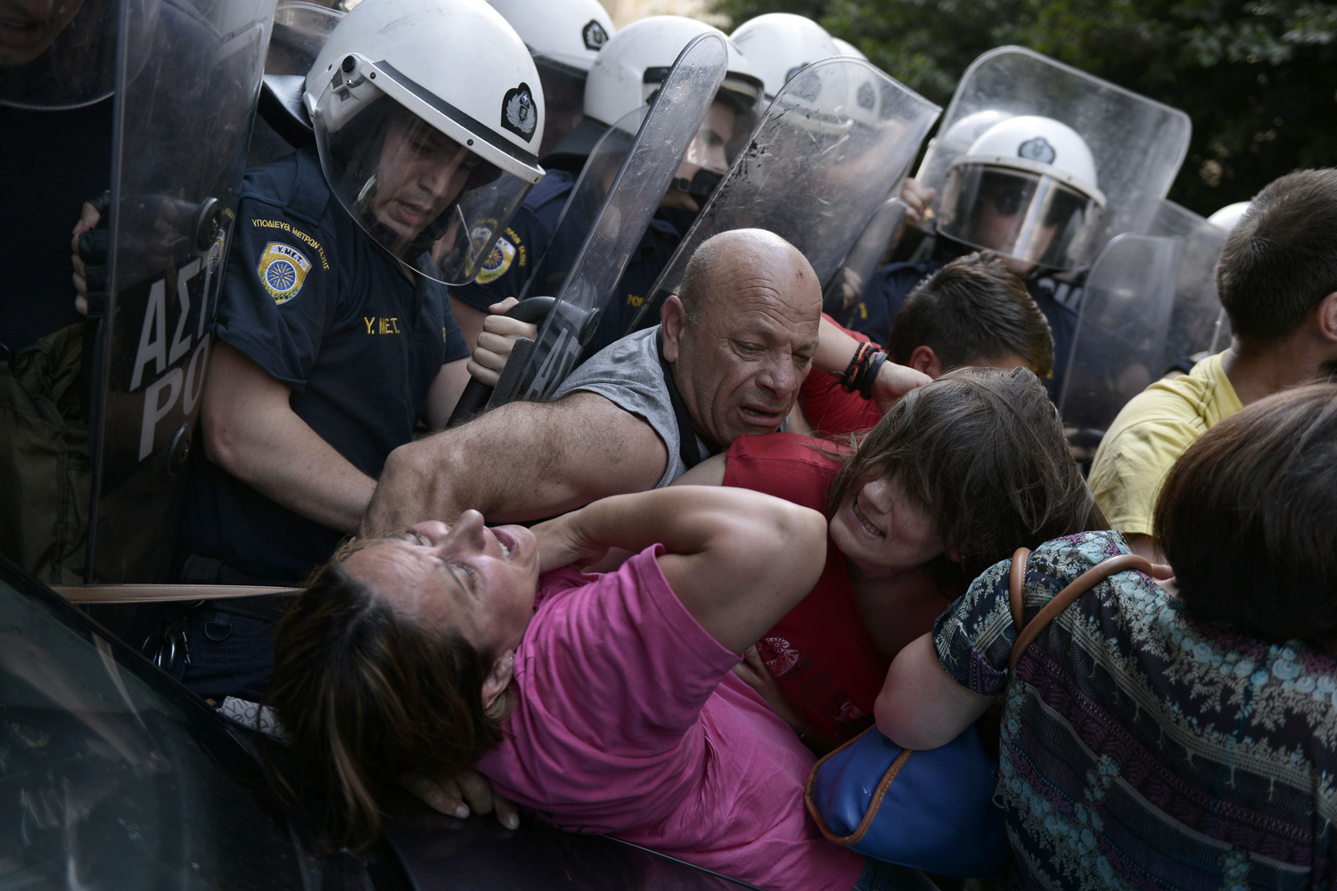 Jun. 12, 2014. Cleaners laid-off by the Finance ministry are pushed back by riot police in their attempt to protest outside the ministry in Athens.