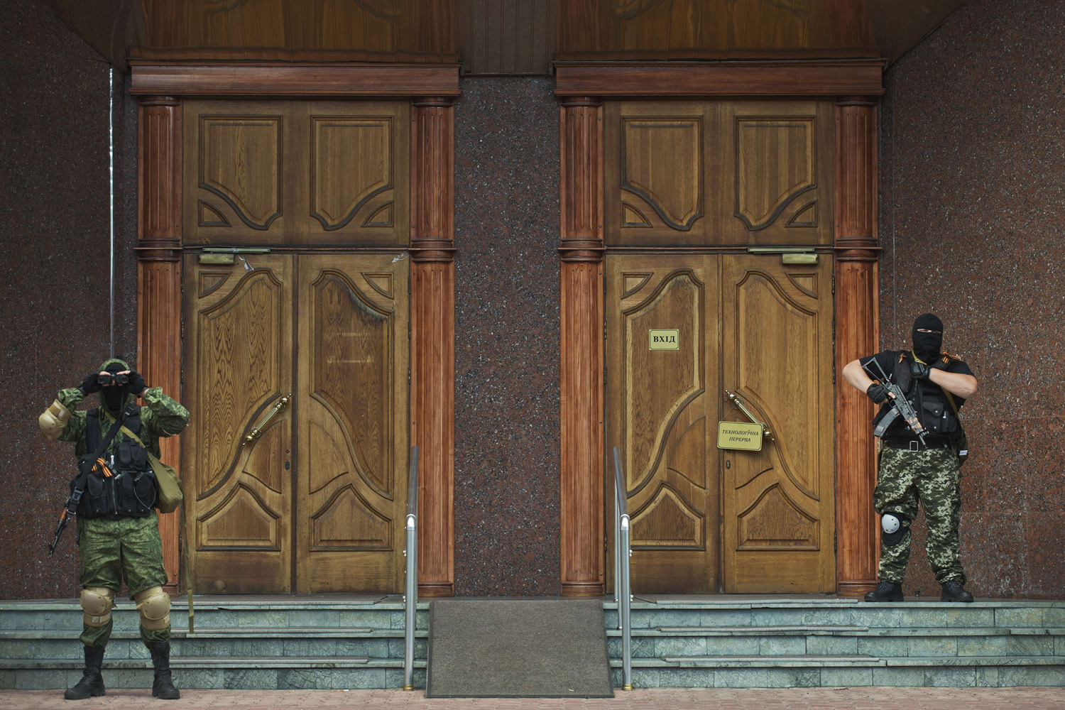 Jun. 16, 2014. Pro-Russian rebels stand guard outside a local branch of the National Bank of Ukraine after seizing the building in Donetsk, eastern Ukraine.