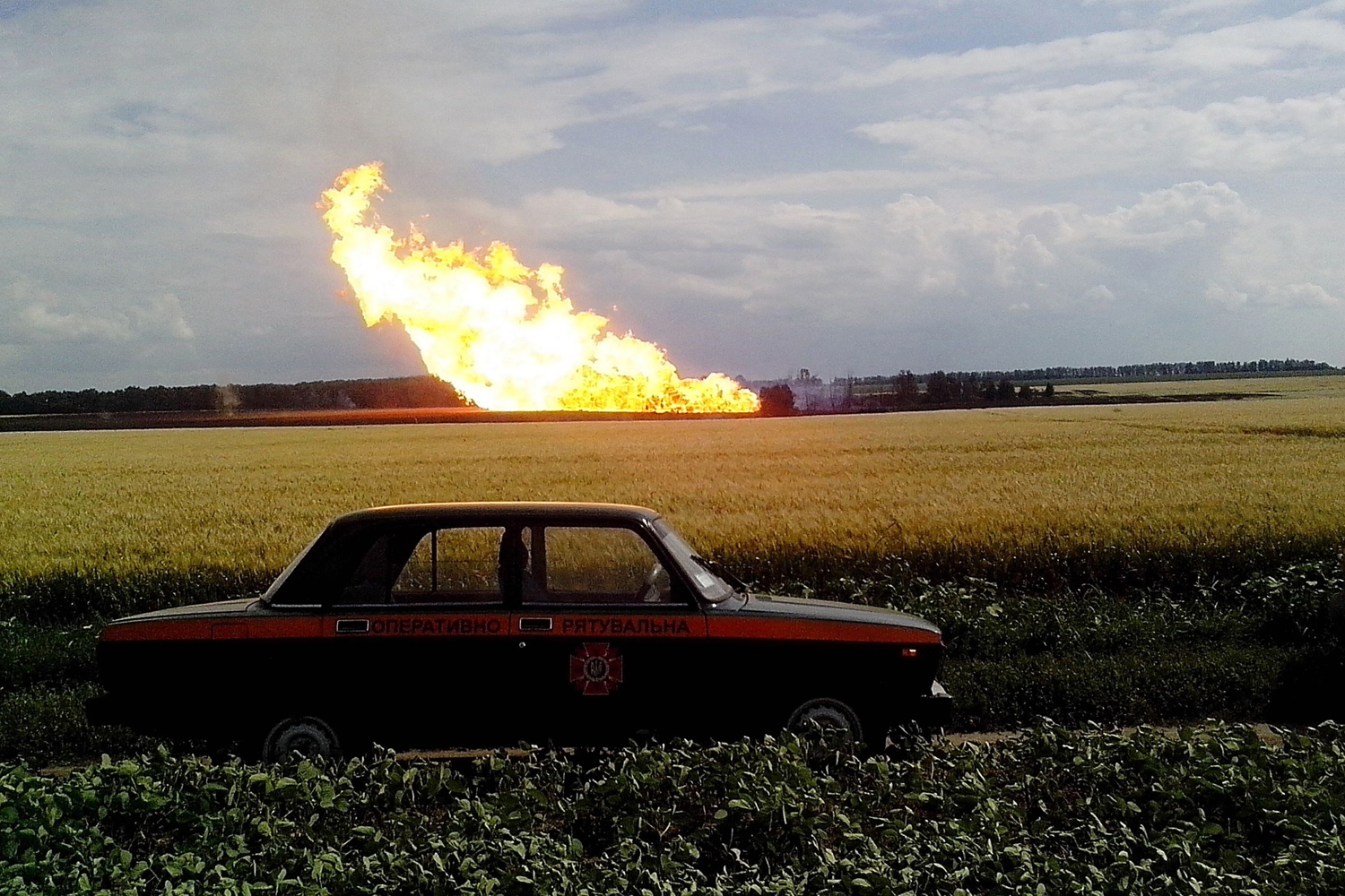 Jun. 17, 2014                               A handout picture taken and released by the Ukrainian Emergency Service on  shows a police car parked beside a field near a fire on the gas pipeline the village of Iskivtsi in the Lokhvytsia region.