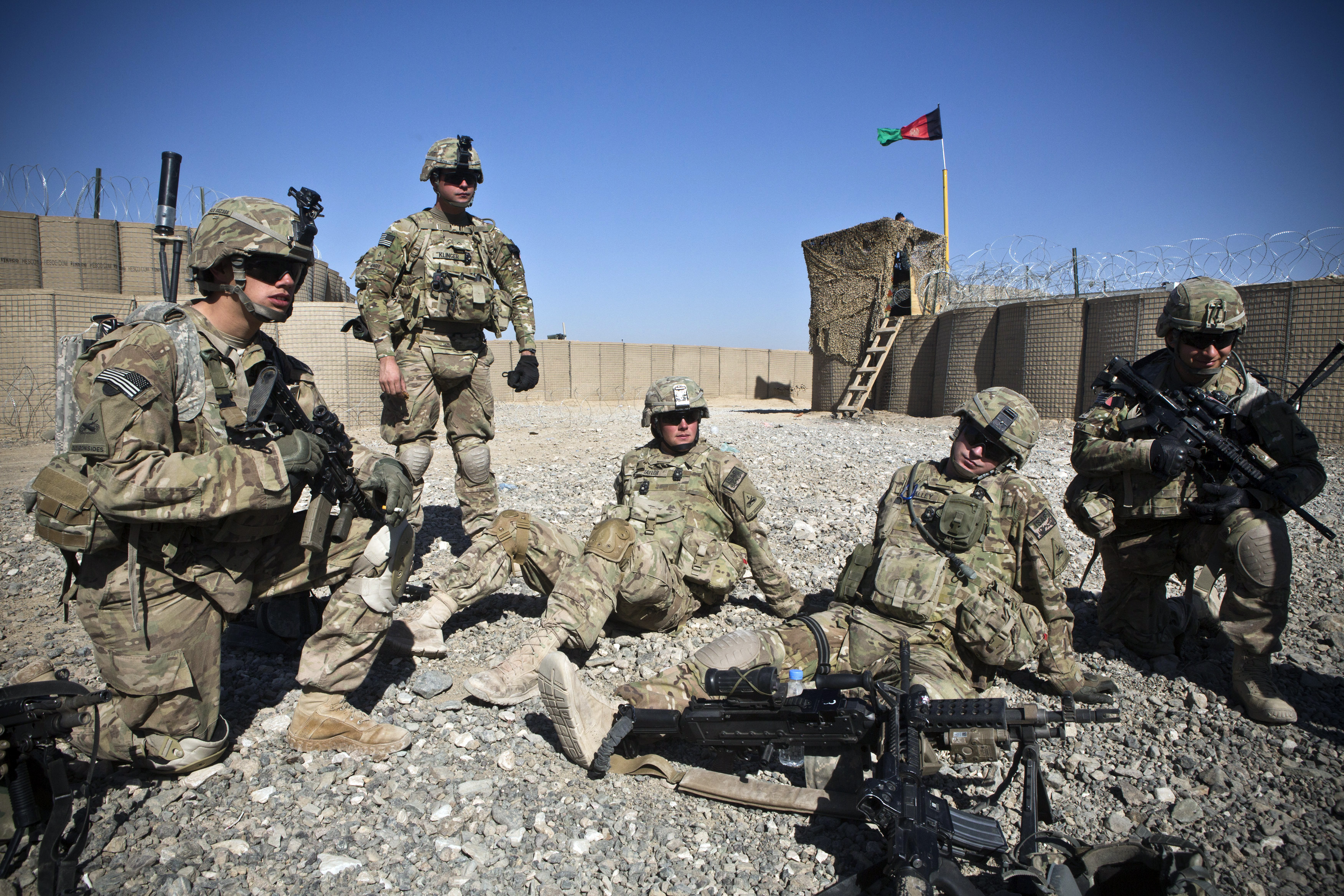 Soldiers with the U.S. Army's Bravo Company, 1st Battalion, 36th Infantry Regiment rest in an Afghan National Police compound before going on patrol near Command Outpost AJK in Maiwand District, Kandahar Province, Afghanistan on Jan. 24, 2013.