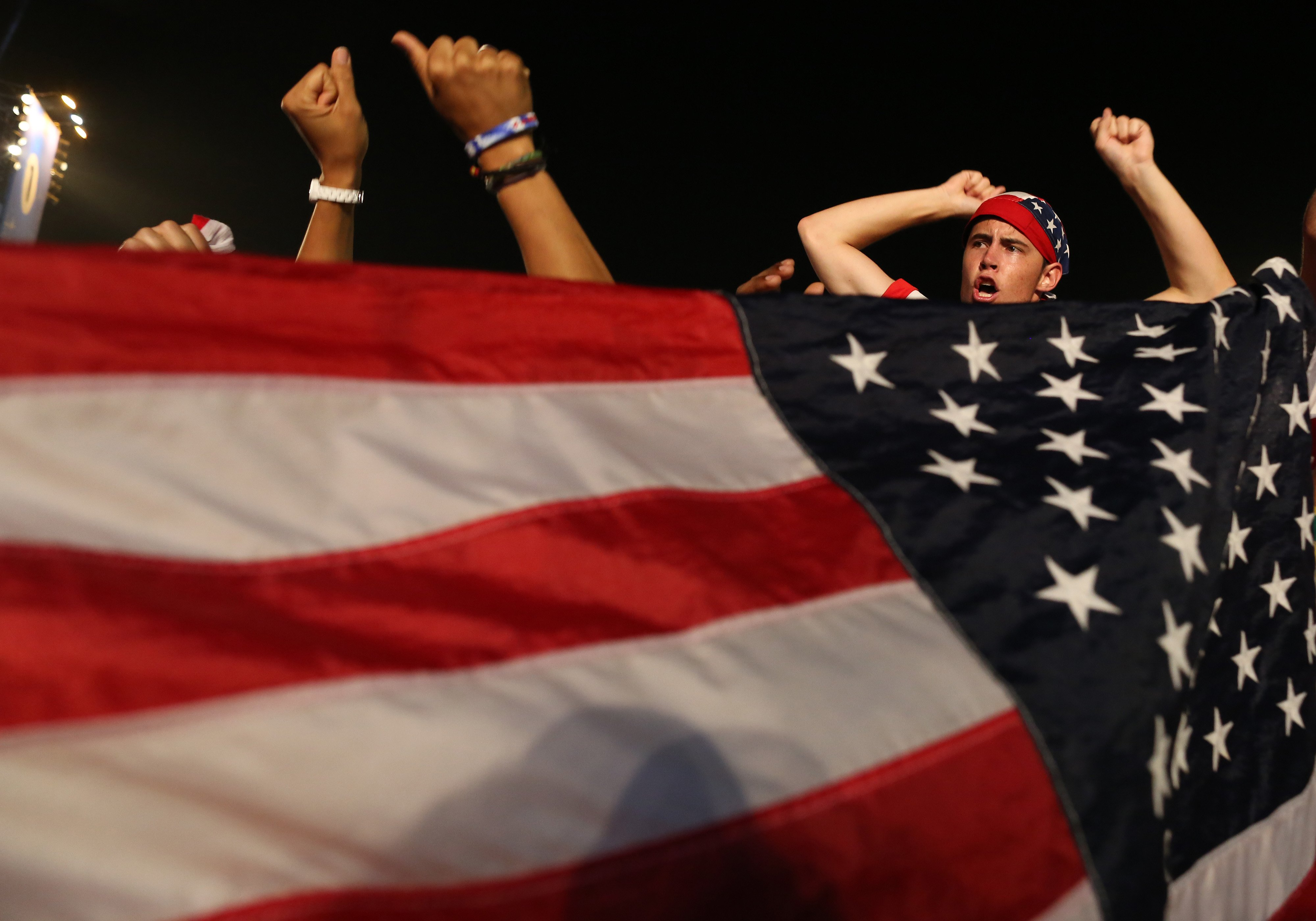 A fan of the U.S. national soccer team celebrates a victory during a live broadcast of the soccer World Cup match between the Unites States and Ghana, on Copacabana beach, Rio de Janeiro on  June 16, 2014.