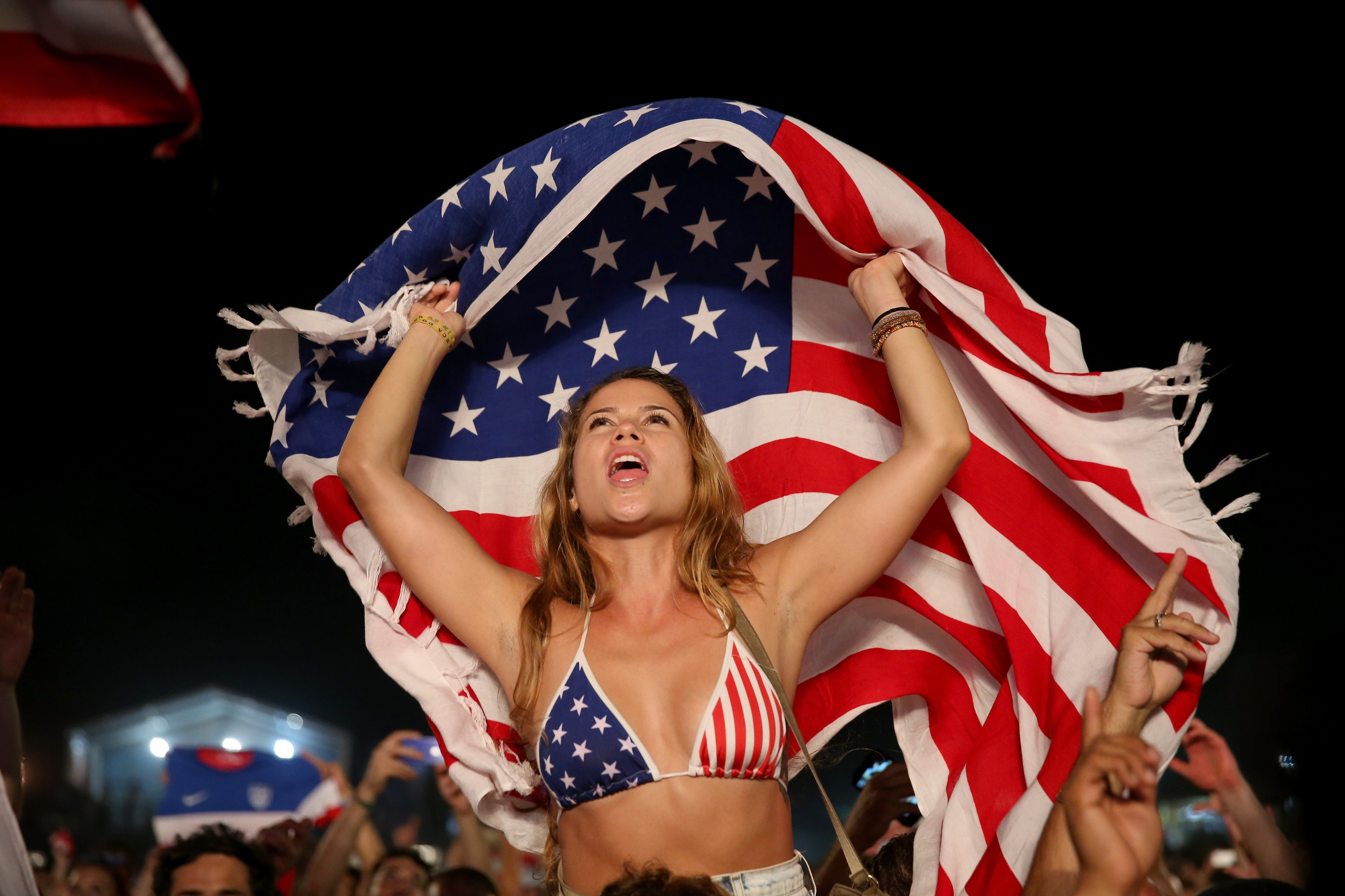 American soccer fans react to their team beating Ghana 2-1 as they watch on a large screen at the FIFA World Cup Fan Fest on Copacabana beach on June 16, 2014 in Rio de Janeiro.