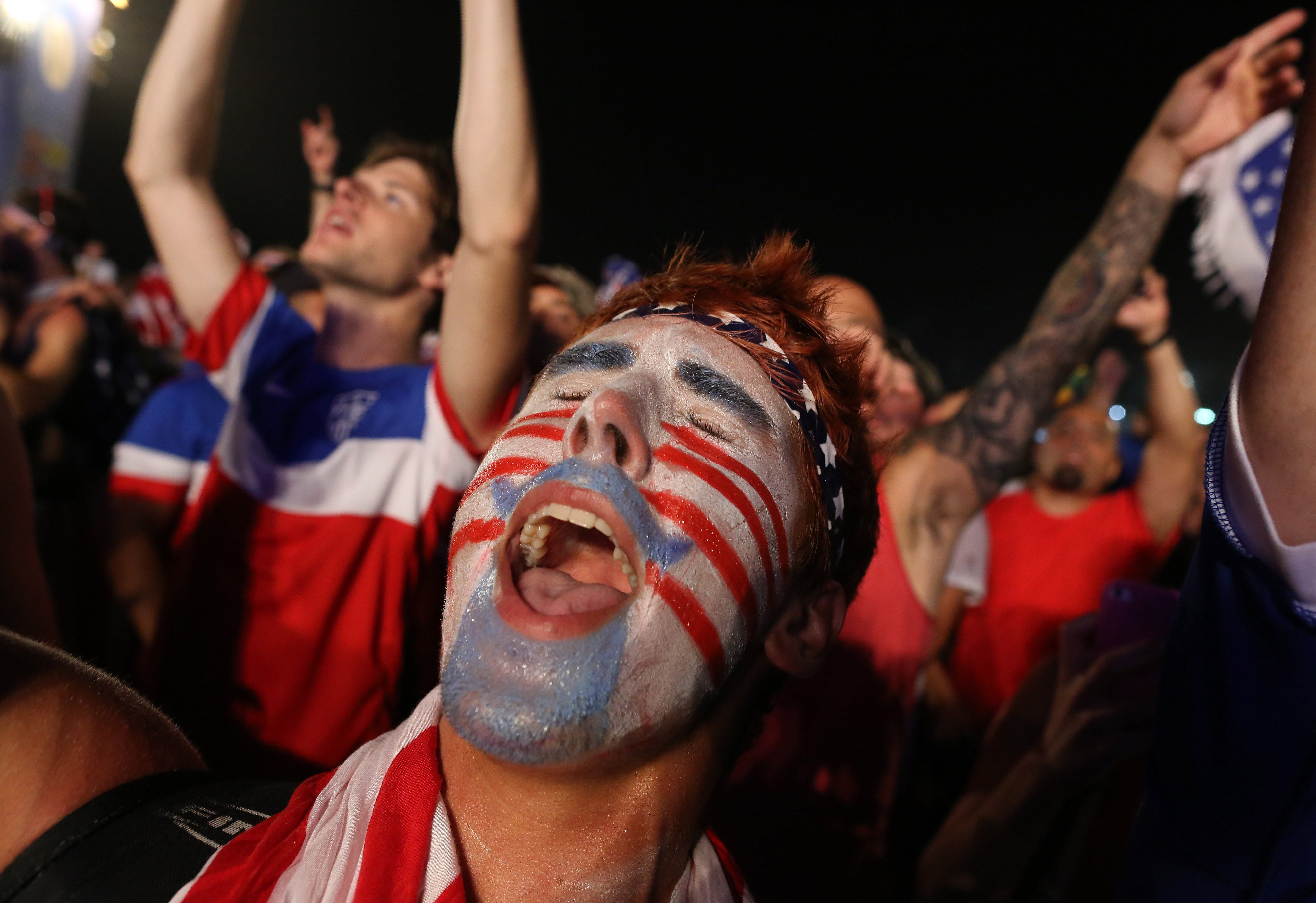 A fan of the U.S. national soccer team celebrates his team's victory during a live broadcast of the soccer World Cup match between the Unites States and Ghana, inside the FIFA Fan Fest area on Copacabana beach, Rio de Janeiro on June 16, 2014.