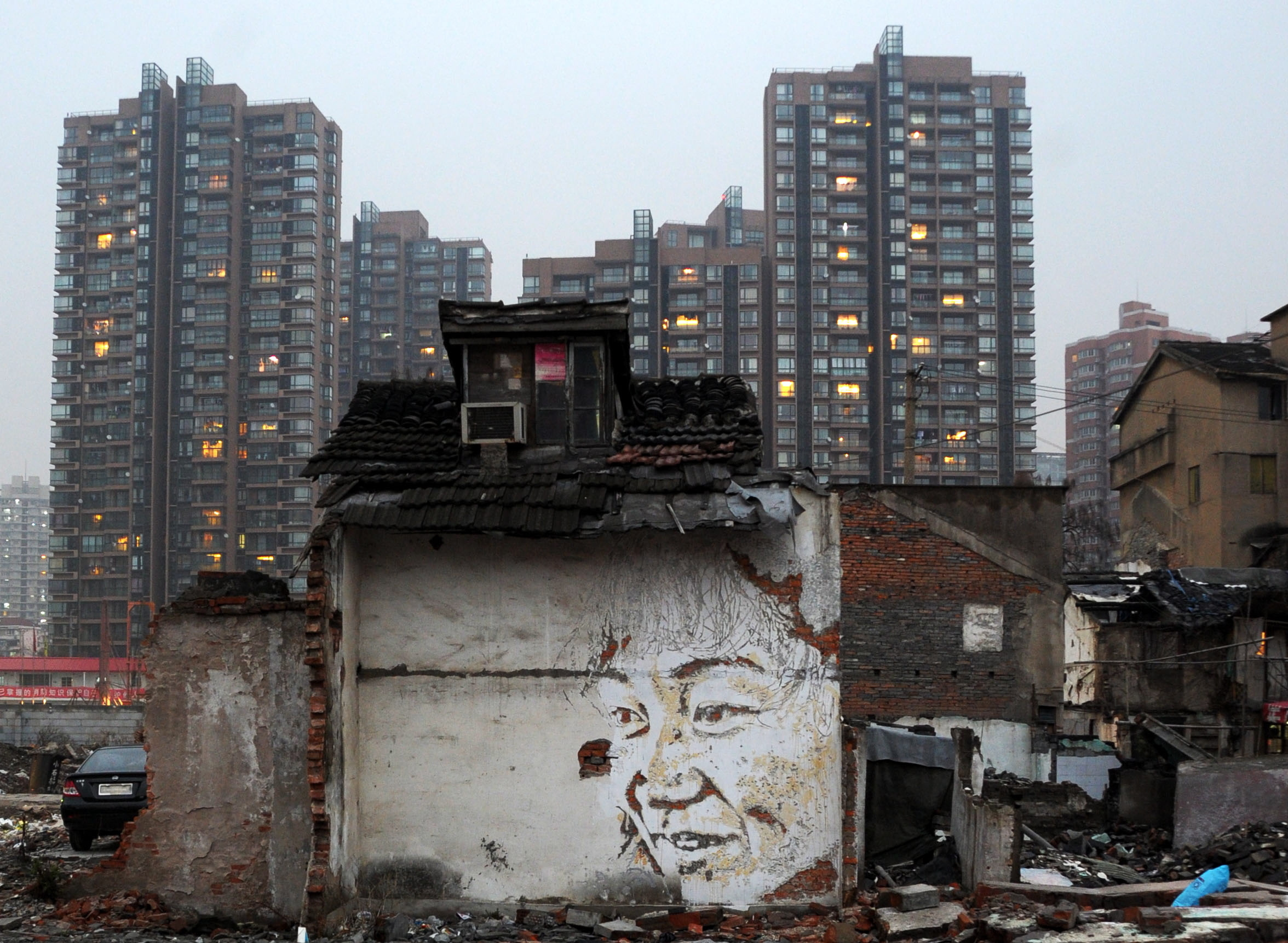 The face of a woman who used to live in the demolished residential block is seen carved into a remaining wall by street artist Vhils and his team in Shanghai on March 1, 2012.