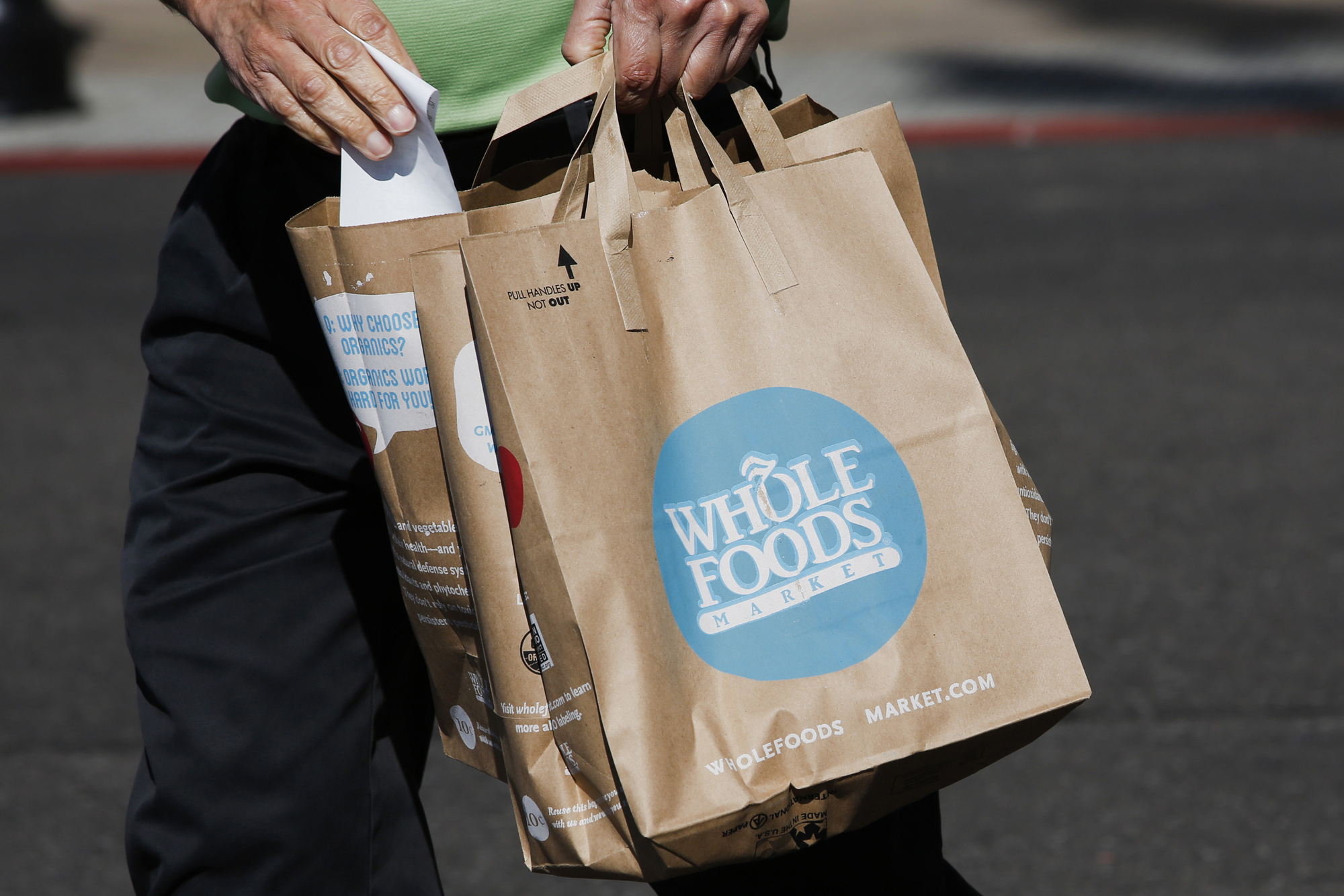 A customer carries shopping bags outside of a Whole Foods in El Segundo, Calif., Nov. 5, 2013.