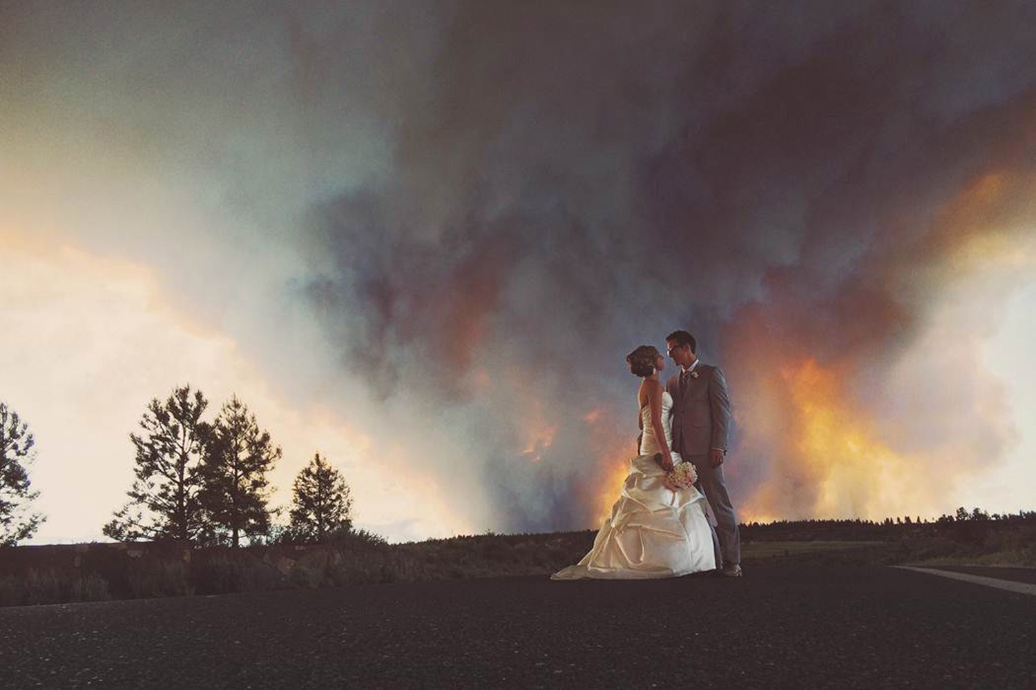 In this Saturday, June 7, 2014, photo provided by Josh Newton, newlyweds Michael Wolber and April Hartley pose for a picture near Bend, Ore., as a wildfire burns in the background.