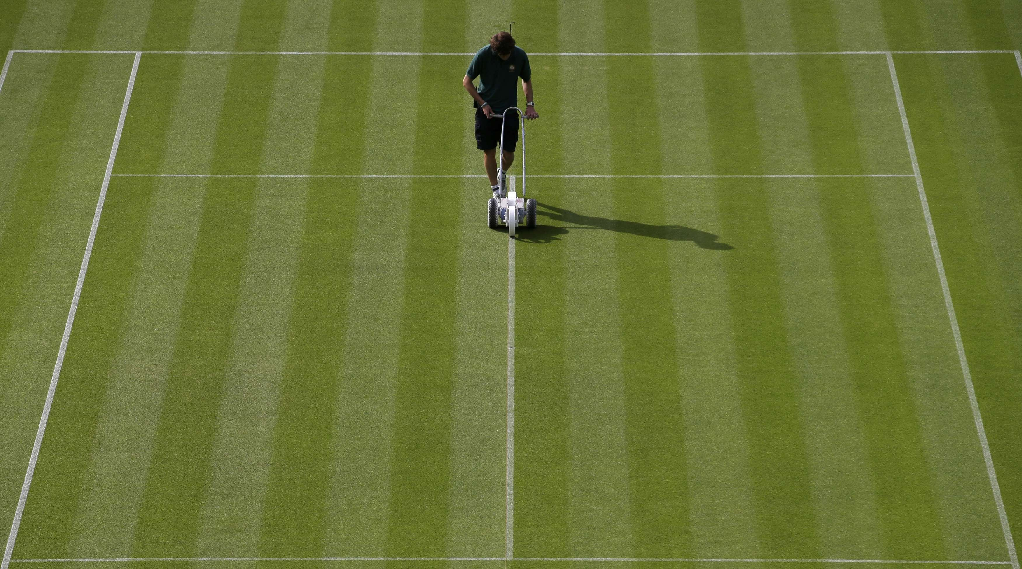 A worker paints lines on a court prior to the first day's play of the Wimbledon Tennis Championships, in London on June 23, 2014.