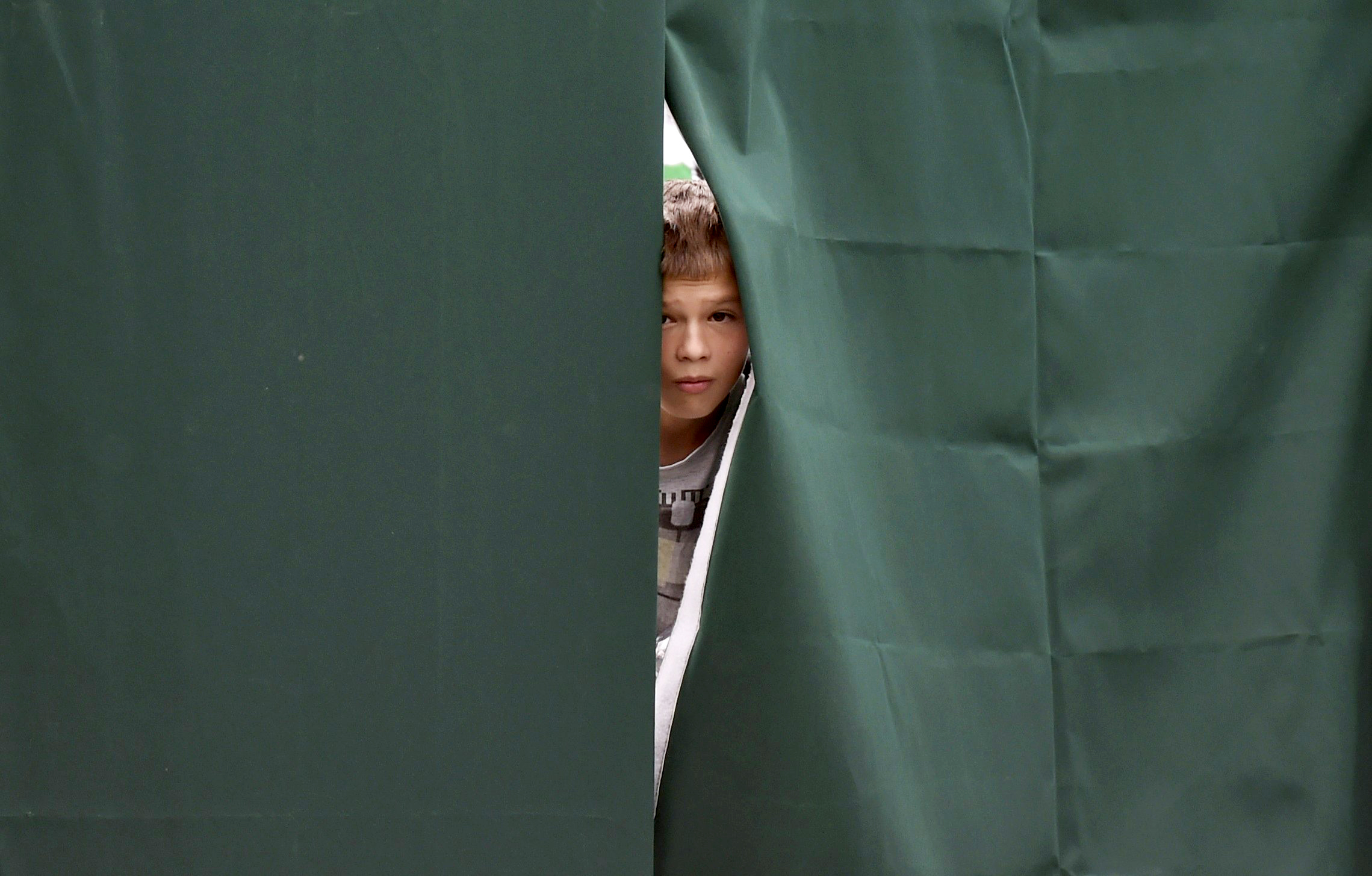 A boy looks through a gap in canvas screening on Court 12 at the Wimbledon Tennis Championships, in London on  June 23, 2014.