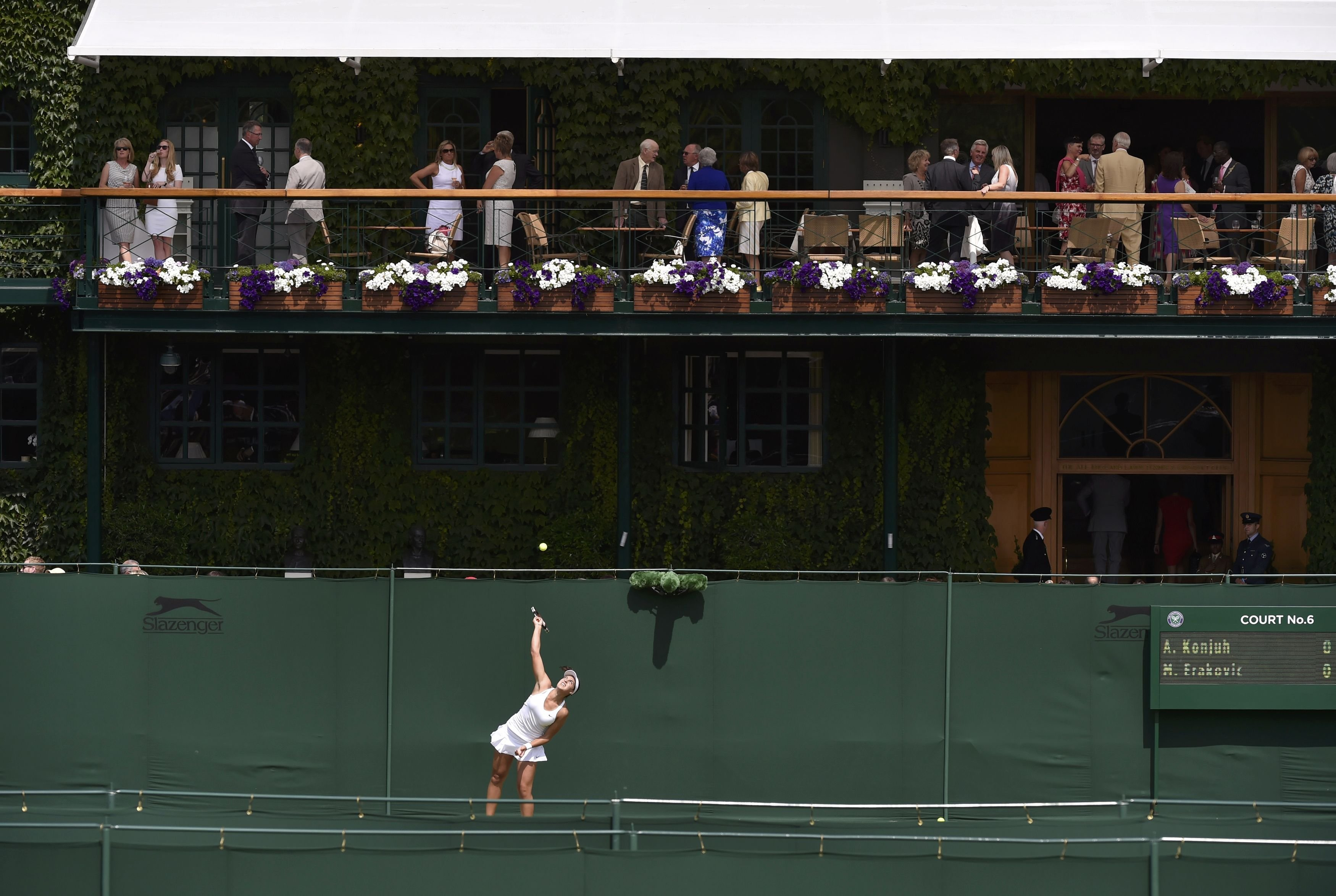 Marina Erakovic of New Zealand serves to Ana Konjuh of Croatia during their women's singles tennis match while spectators enjoy the game at the Wimbledon Tennis Championships, in London on June 23, 2014.