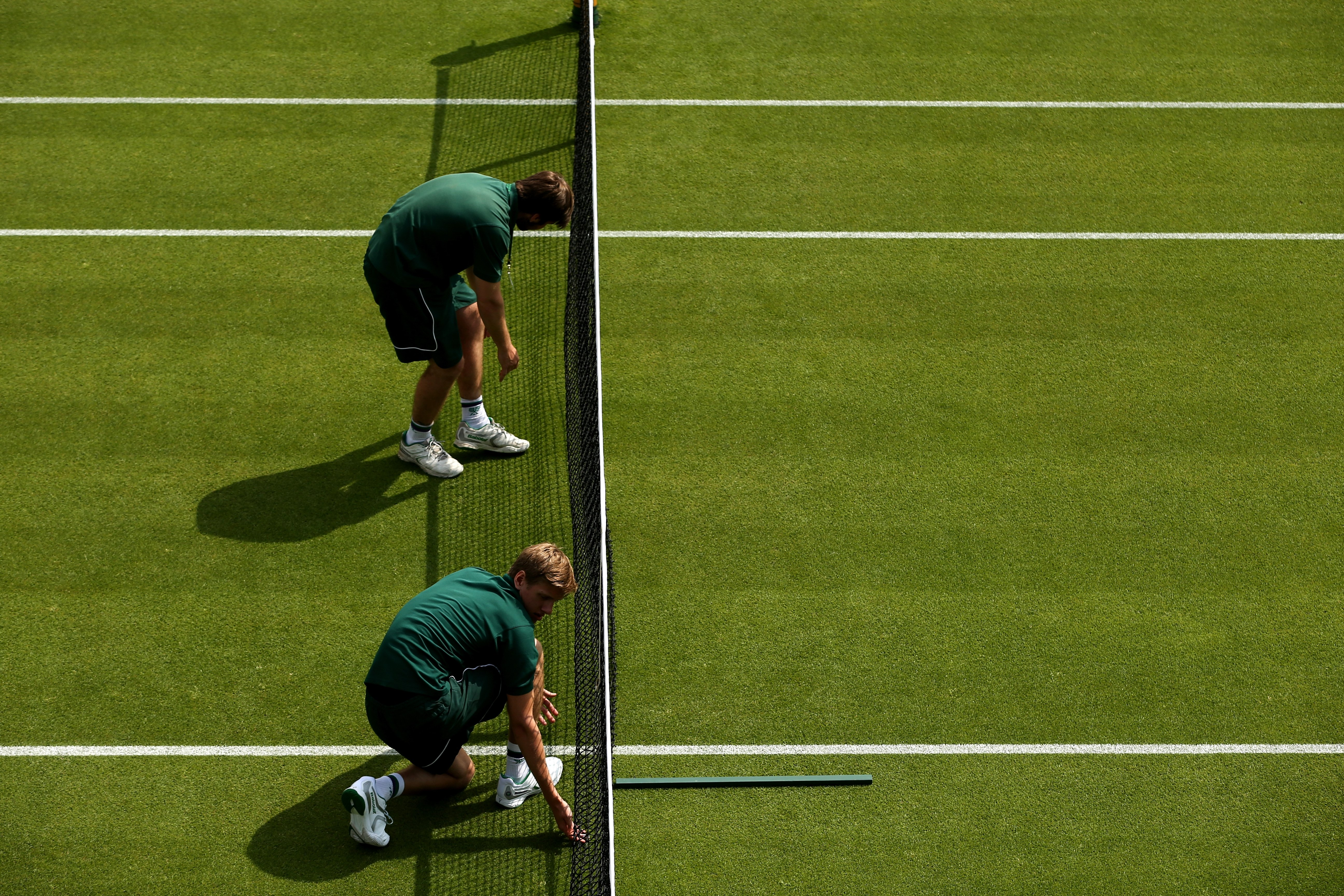 Groundstaff prepare the courts on day one of the Wimbledon Tennis Championships, in London on June 23, 2014.