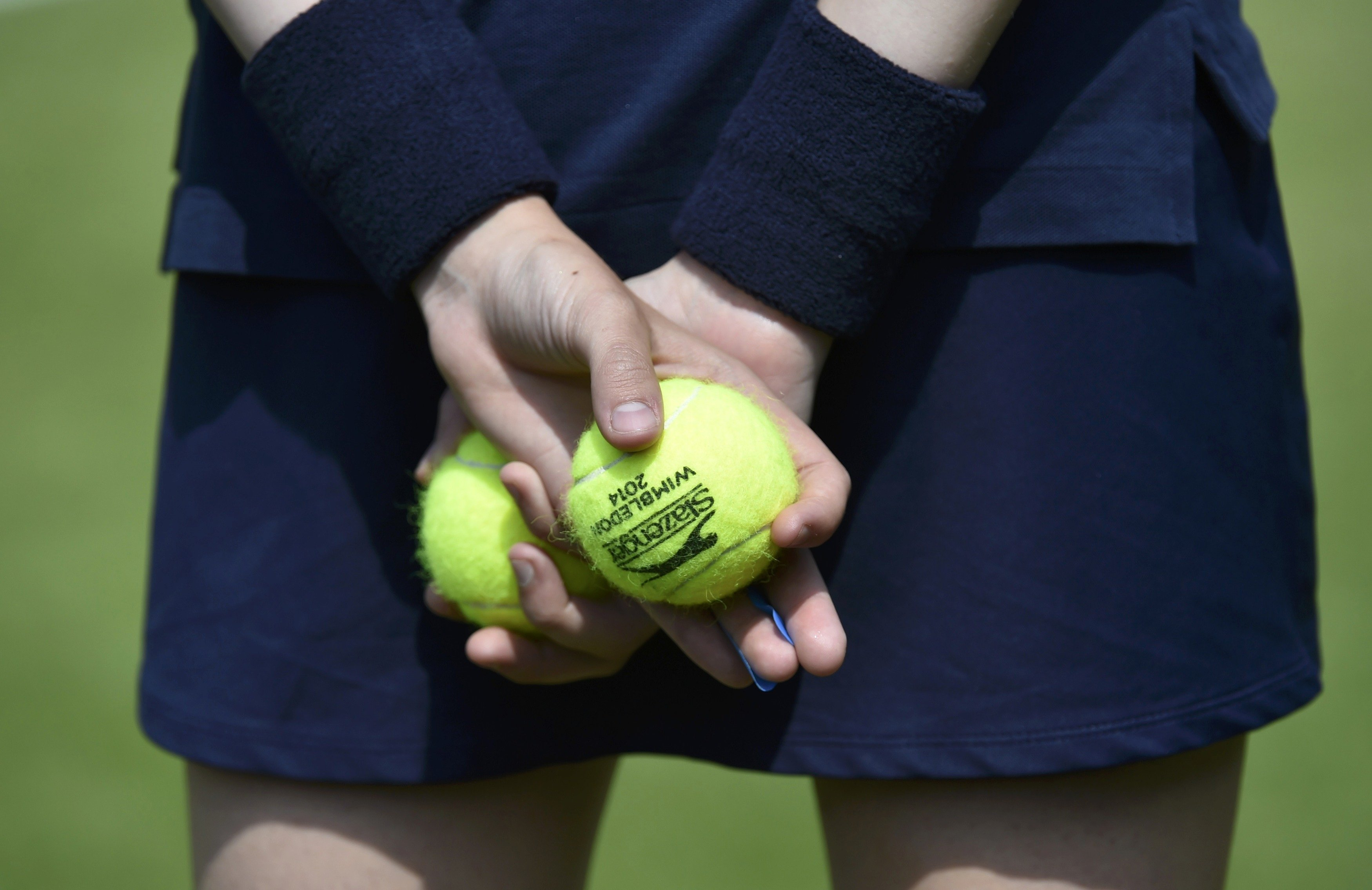 A ball-girl holds tennis balls at the Wimbledon Tennis Championships, in London on June 23, 2014.