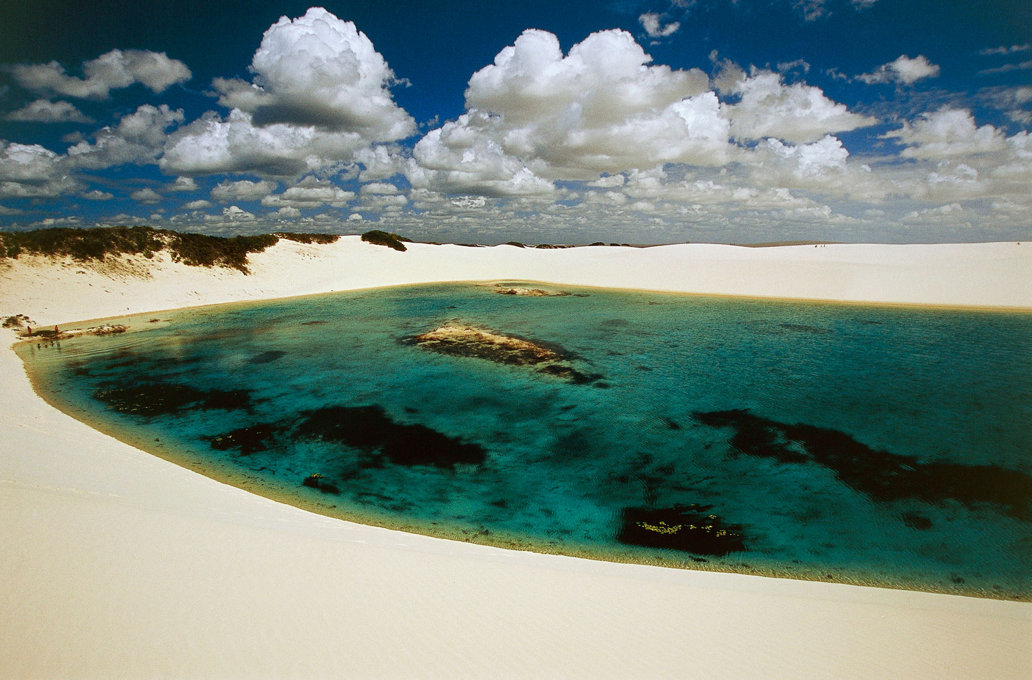 """The Lencois Maranhenses National Park received its                                Portuguese name, meaning """"the bedsheets of Maranhao,"""" from its famous white sand dunes, but the region keeps a bit of color thanks to the blue waters in between the dunes and the beautiful tropical fish that swim there."""