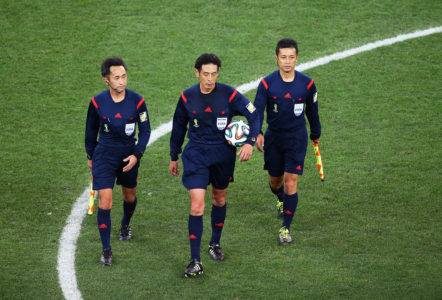 Assistant referee Toshiyuki Nagi, referee Yuichi Nishimura and assistant referee Toru Sagara of Japan walk on the field at the end of the match during the 2014 FIFA World Cup Brazil Group A match between Brazil and Croatia at Arena de Sao Paulo on June 12, 2014 in Sao Paulo.