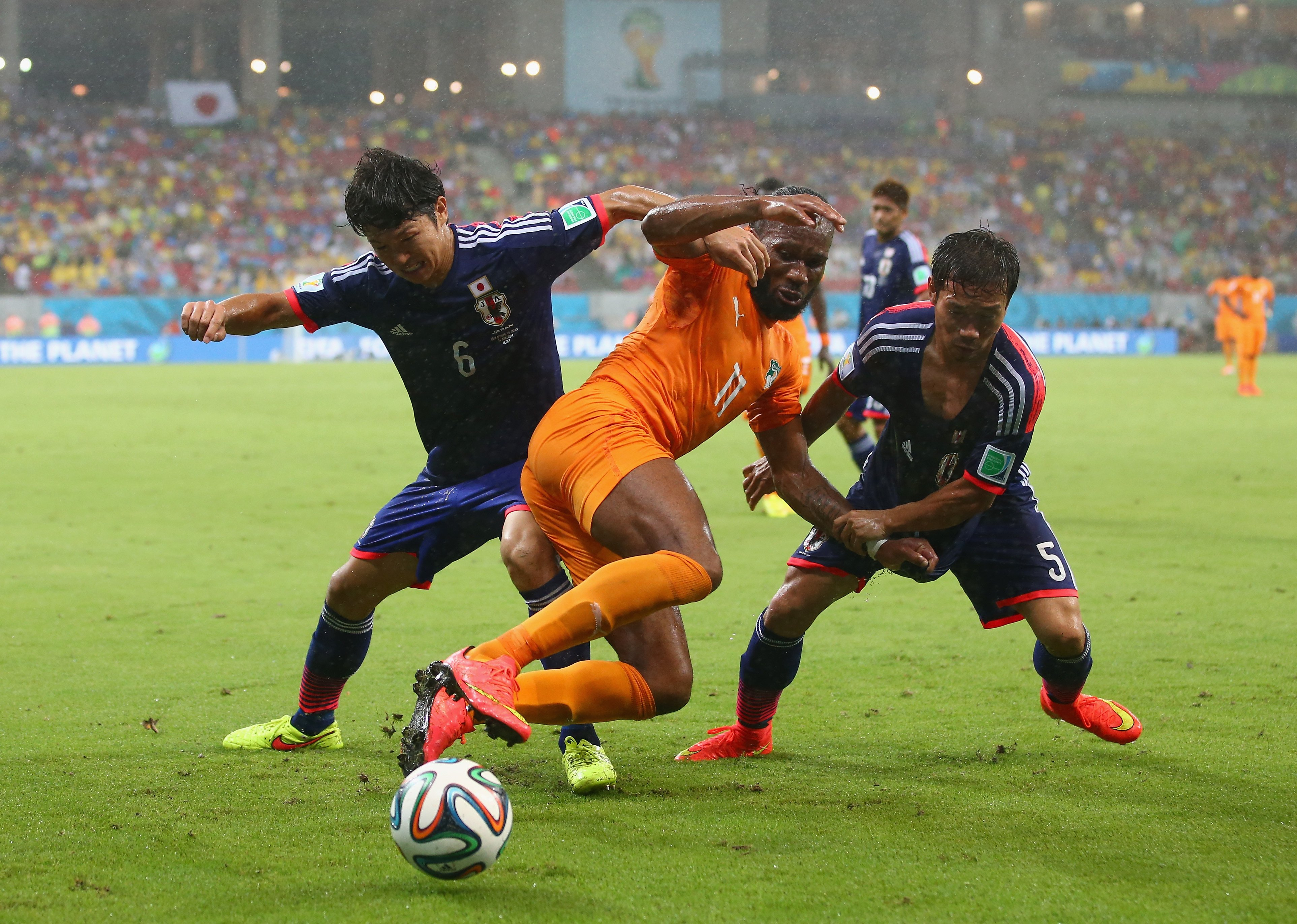 Masato Morishige and Yuto Nagatomo of Japan challenge Didier Drogba of the Ivory Coast during the 2014 FIFA World Cup Brazil Group C match  between the Ivory Coast and Japan at Arena Pernambuco on June 14, 2014 in Recife, Brazil.