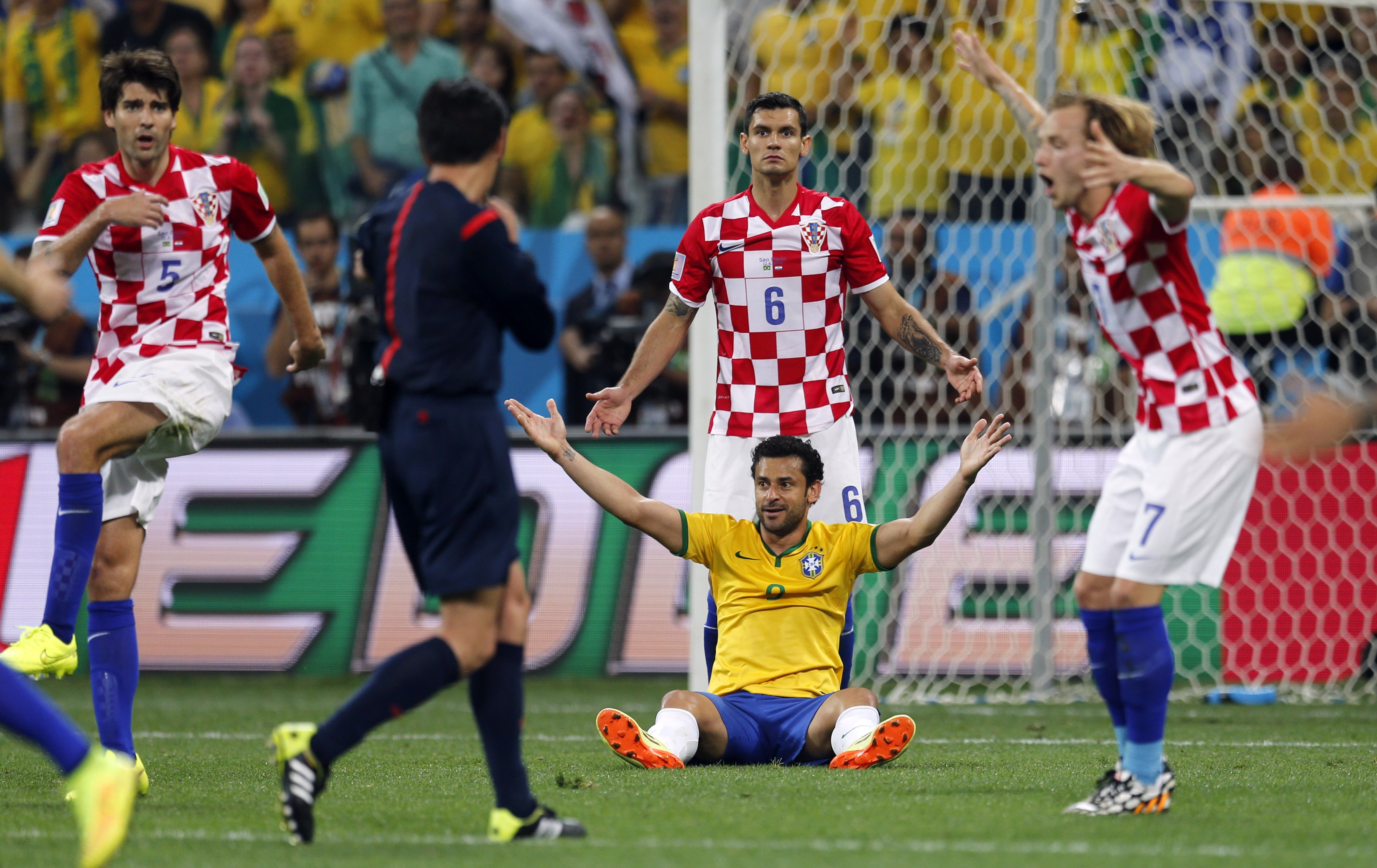 Brazil's Fred sits on the pitch as Croatian players Vedran Corluka, Dejan Lovren and Ivan Rakitic protest after the referee called a penalty against Croatia during the group A World Cup soccer match in the opening game of the tournament at Itaquerao Stadium in Sao Paulo on June 12, 2014.