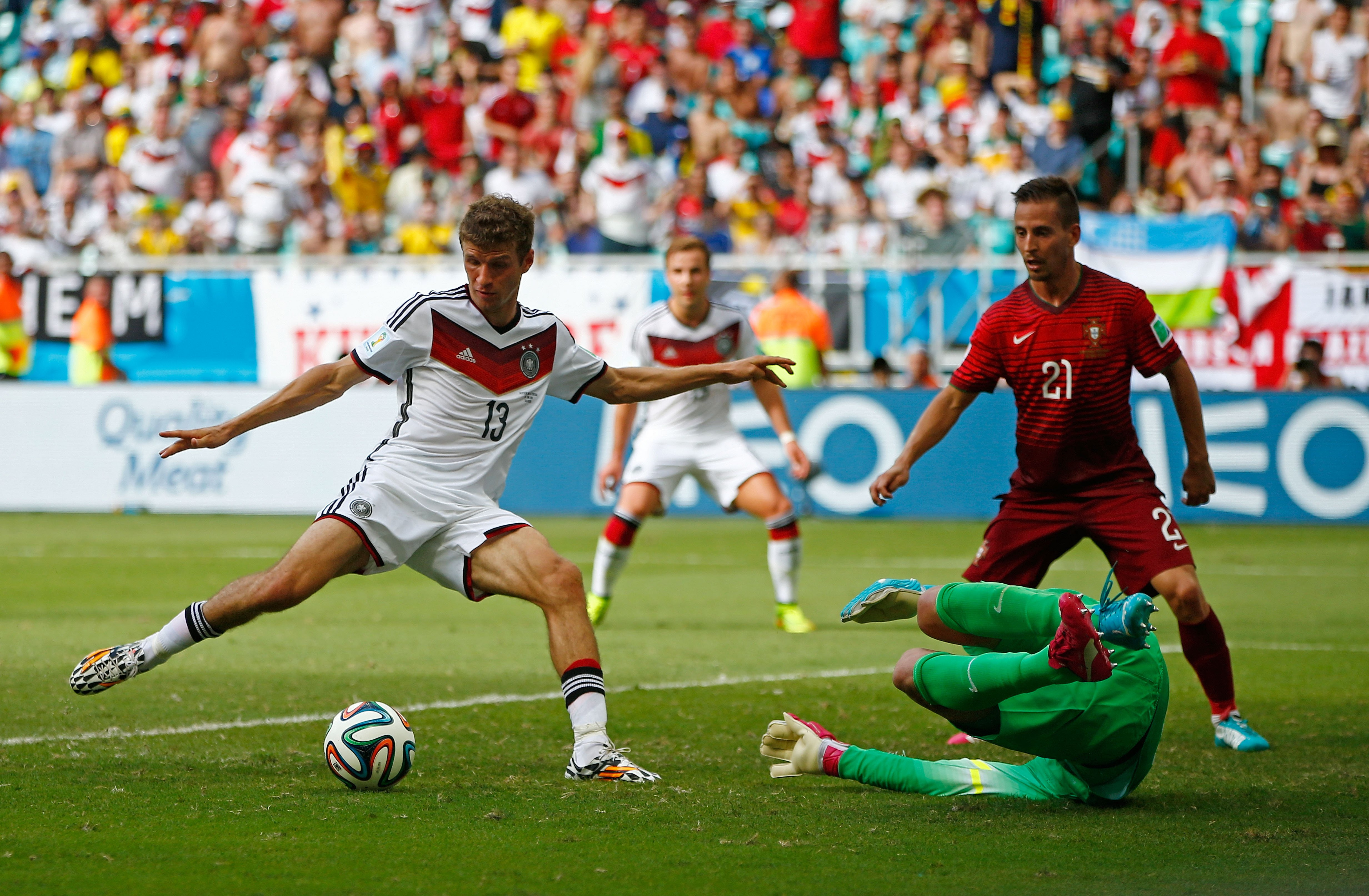 Thomas Mueller of Germany shoots and scores his team's fourth goal and completes his hat trick past Rui Patricio of Portugal during the 2014 FIFA World Cup Brazil Group G match between Germany and Portugal at Arena Fonte Nova on June 16, 2014 in Salvador, Brazil.