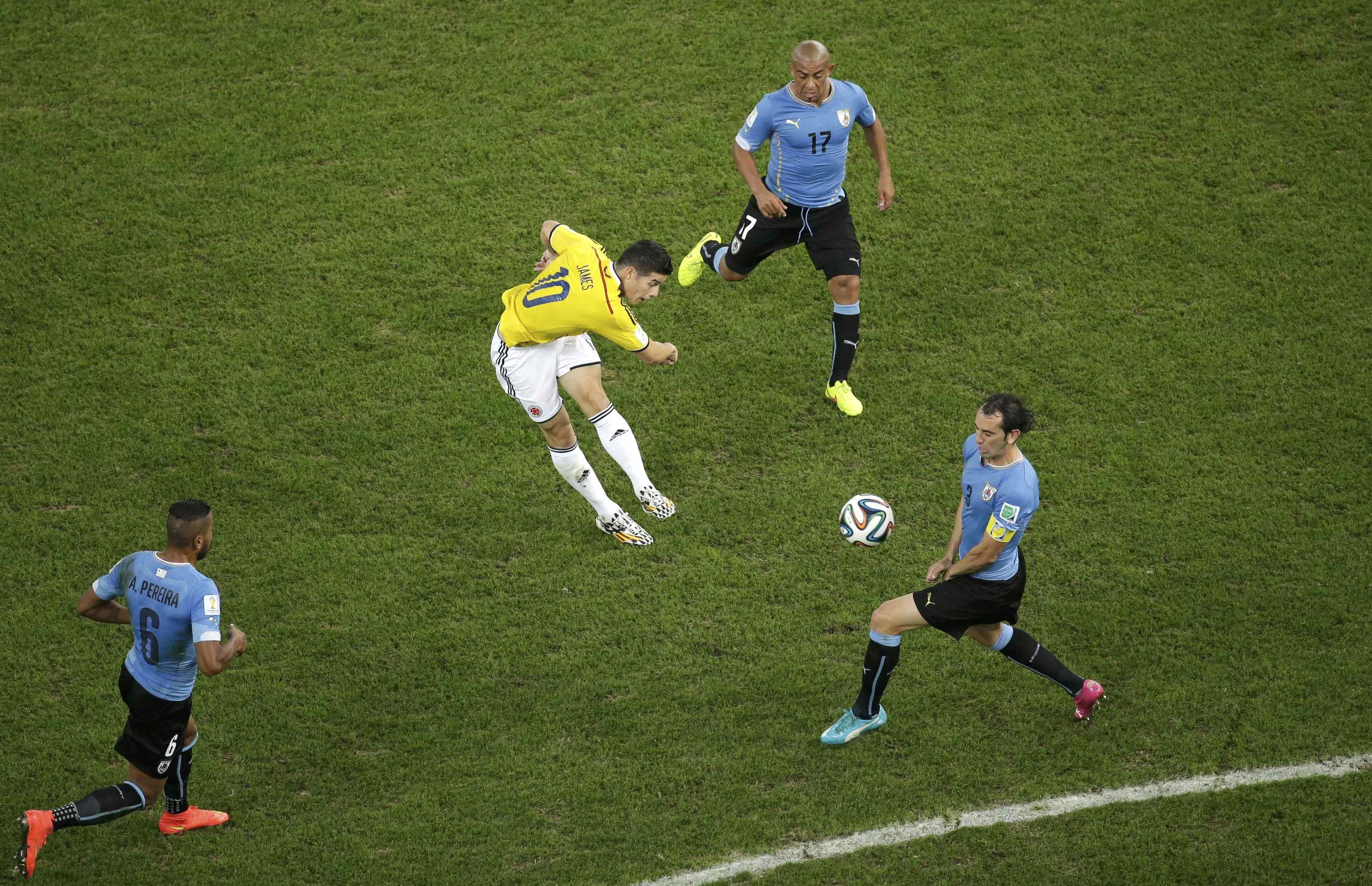 Colombia's James Rodriguez scores a goal past Uruguay's Diego Godin, Alvaro Pereira, and Egidio Arevalo Rios during their game at the Maracana stadium in Rio de Janeiro on June 28, 2014.