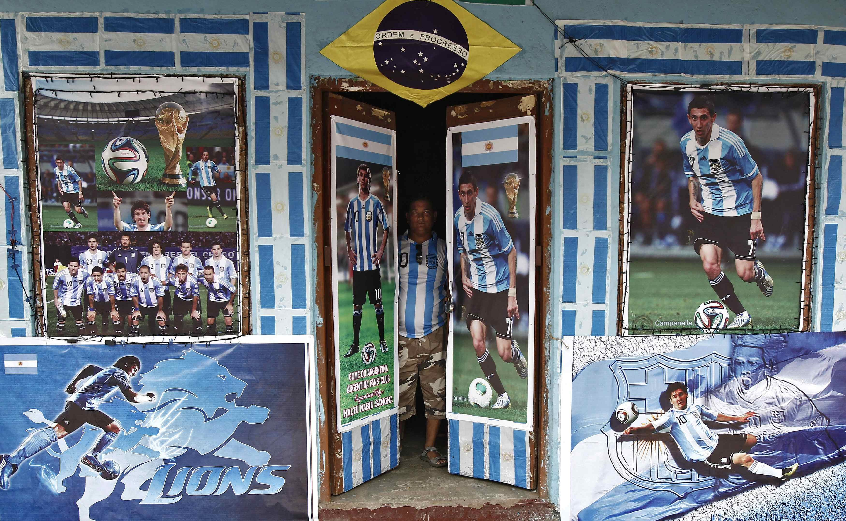 A fan of Argentina looks out from his local soccer club decorated with pictures of Argentin soccer players ahead of the 2014 World Cup, in Kolkata on June 10, 2014.