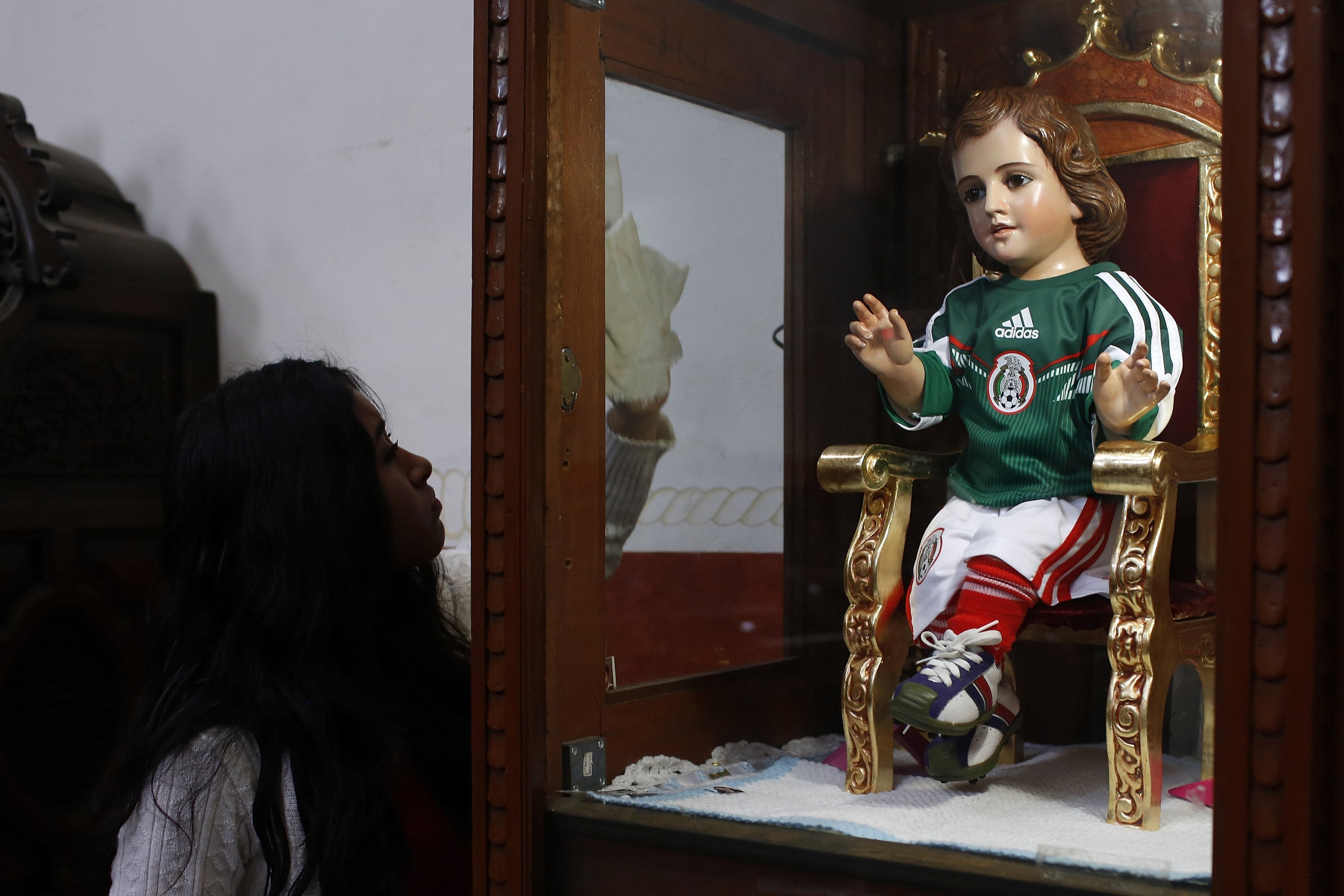 A woman cleans a glass cabinet with a baby Jesus statue dressed in a version of the national soccer team jersey at a church in Mexico City on June 12, 2014.