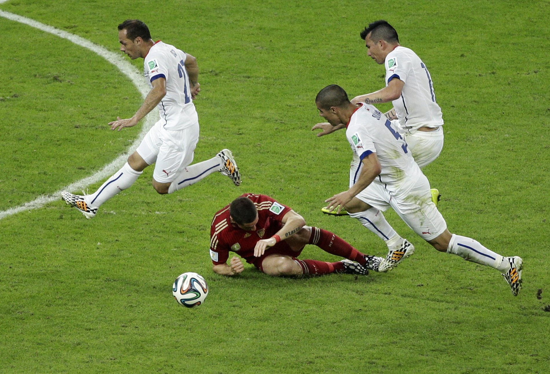 Chile's Eugenio Mena, Francisco Silva and Gary Medel, from left, jump over Spain's Fernando Torres during the group B World Cup soccer match between Spain and Chile at the Maracana Stadium in Rio de Janeiro on June 18, 2014.