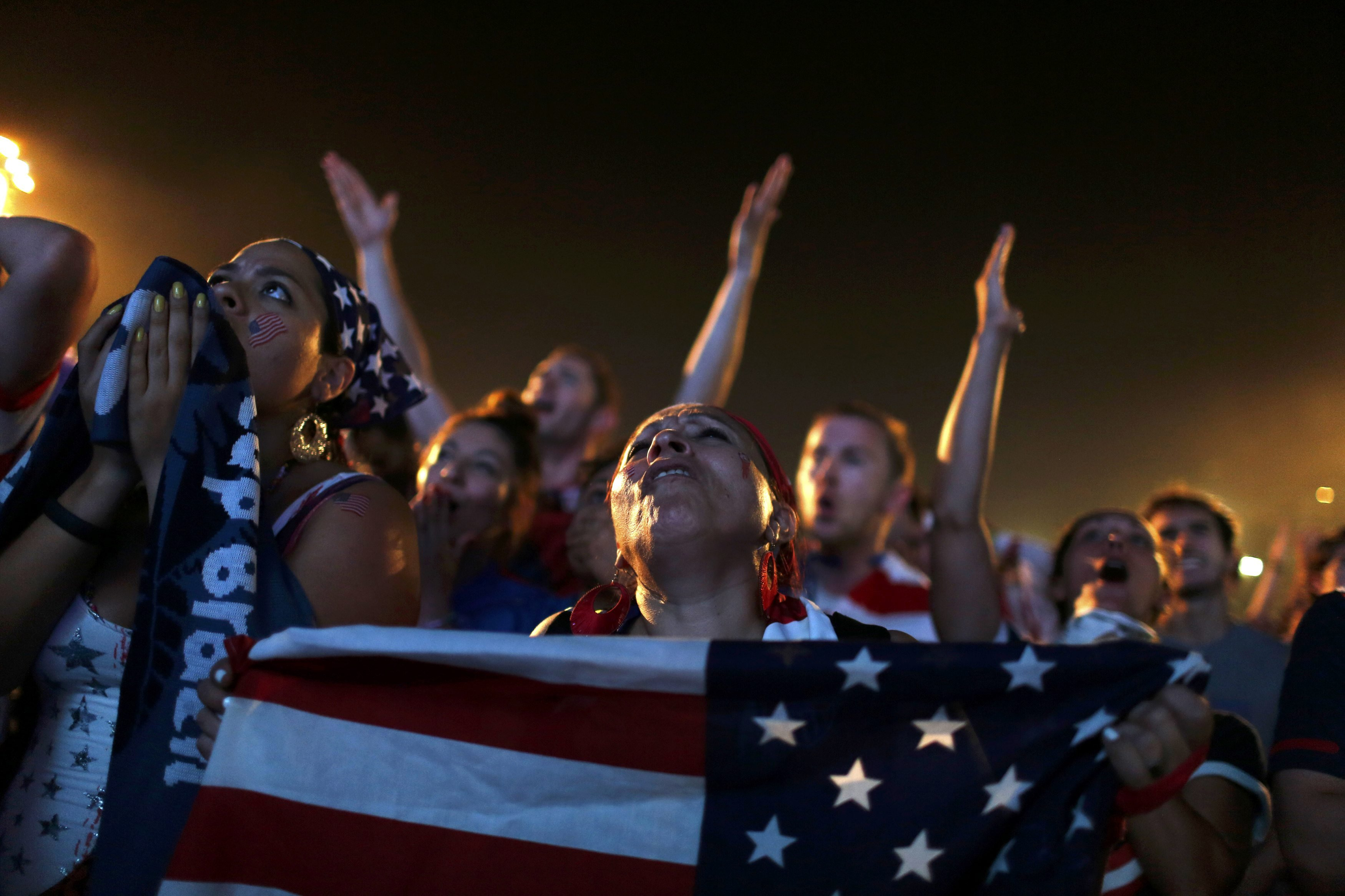 U.S. soccer fans react as they watch the 2014 World Cup soccer match between U.S. and Ghana on a large screen at Copacabana beach in Rio de Janeiro on June 16, 2014.