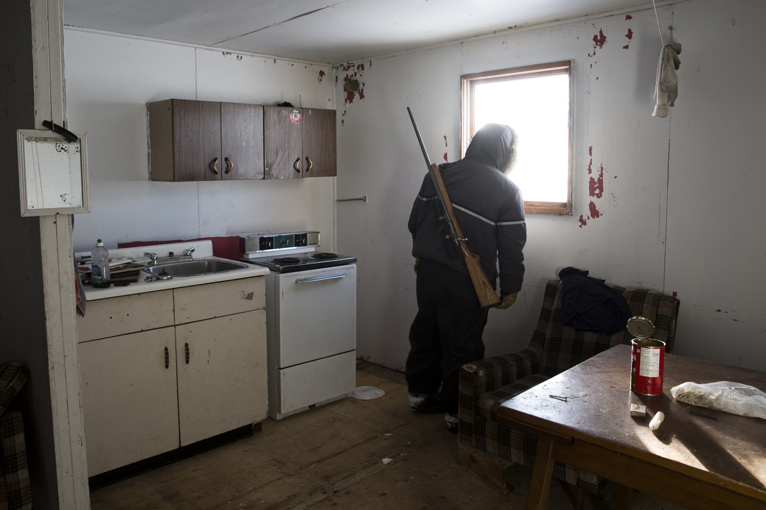 Arviat, Canada, Oct. 19, 2013. Brian Tagalik, 28, peers out the window of a house during a hunting trip. Born in the Arctic and schooled in the south of Canada, Brian says he feels lost between the modern way of life and the dying traditions of his ancestors.