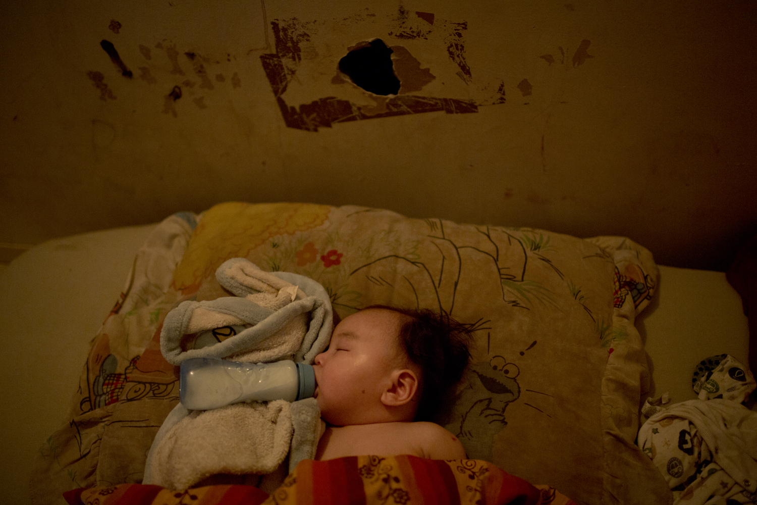 Arviat, Canada on Nov. 2, 2013. Seven-month-old Henry Edward Thompson drinks baby formula in bed.