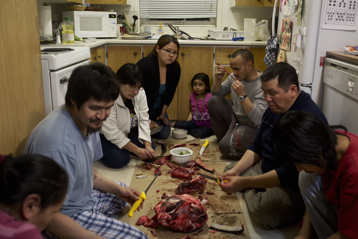 Nov. 13, 2013. People gather around the floor of a kitchen during a feast of hunted foods.