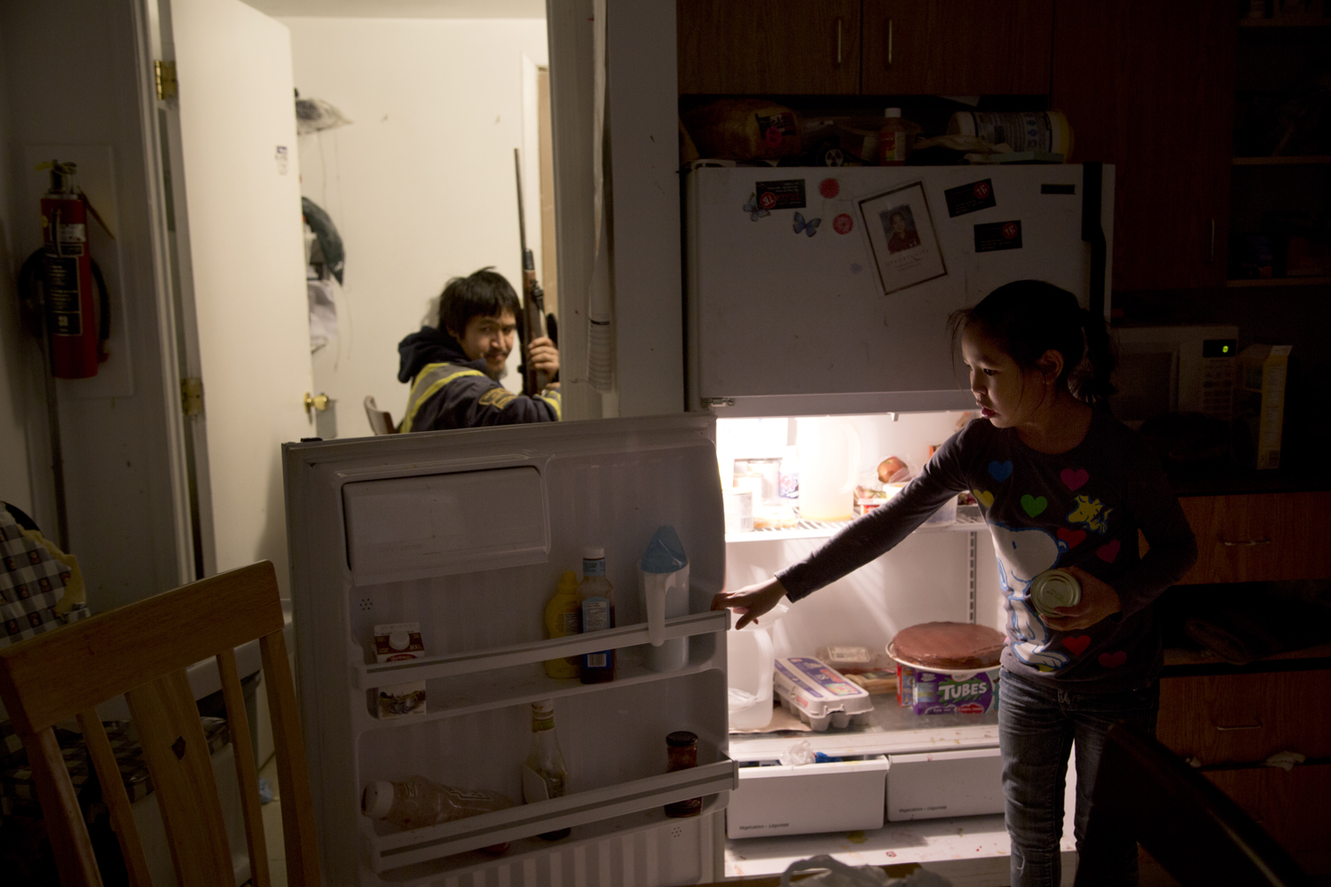 Pangnirtung, Canada, Nov. 16, 2013. Annie Ishlutak (right), 7, reaches into a near empty refrigerator as her father Levi (left), 35, cleans his rifle upon returning from a hunting trip.
