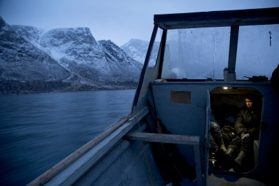 PANGNIRTUNG, CANADA - NOVEMBER 14 During a hunting trip, Paul Ishlutak, 12, stays warm in the underside of a boat in Pangnirtung, Canada on Nov. 14, 2013. He and his brother Damien tag along with their father, who teaches them how to hunt. With so many children to feed and support, his father Levi often struggles to put food on the table, living day to day, and pay check to pay check. As communities in Nunavut are completely cut off from the rest of Canada by road, food and supplies are shipped at an extremely high cost by boat and plane, leading to exorbitant prices at the grocery stores. The Inuit have traditionally depended on hunting to provide food, shelter, and warmth for their families in the harsh arctic environment. Hunting provides much-needed sustenance for families. However, environmental groups often criticize the Inuit for hunting species claimed to have dwindling populations such as narwhal, belugas, seals, and polar bears. The current debate highlights the clash between traditional hunting practices and modern conservation science. (Ed Ou/Reportage by Getty Images)***EDITORS NOTE***The photographer contributed money for food, equipment, and gas for the hunting trip, as his presence took up the limited space and supplies on the boat.